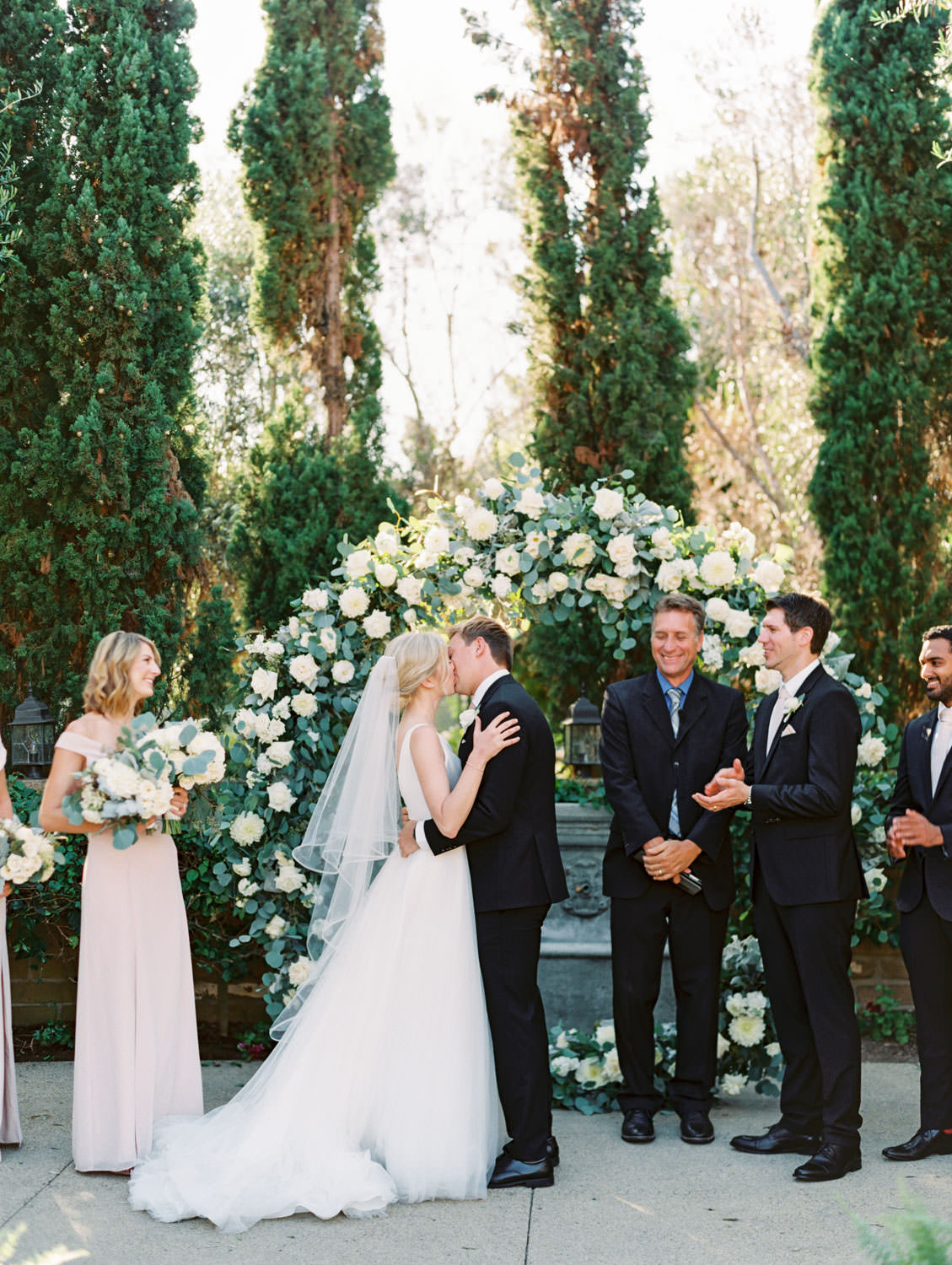 Bride and groom first kiss. Circular ceremony arch with silver dollar eucalyptus, white dahlias and roses. Estancia La Jolla wedding shot on film by Cavin Elizabeth Photography