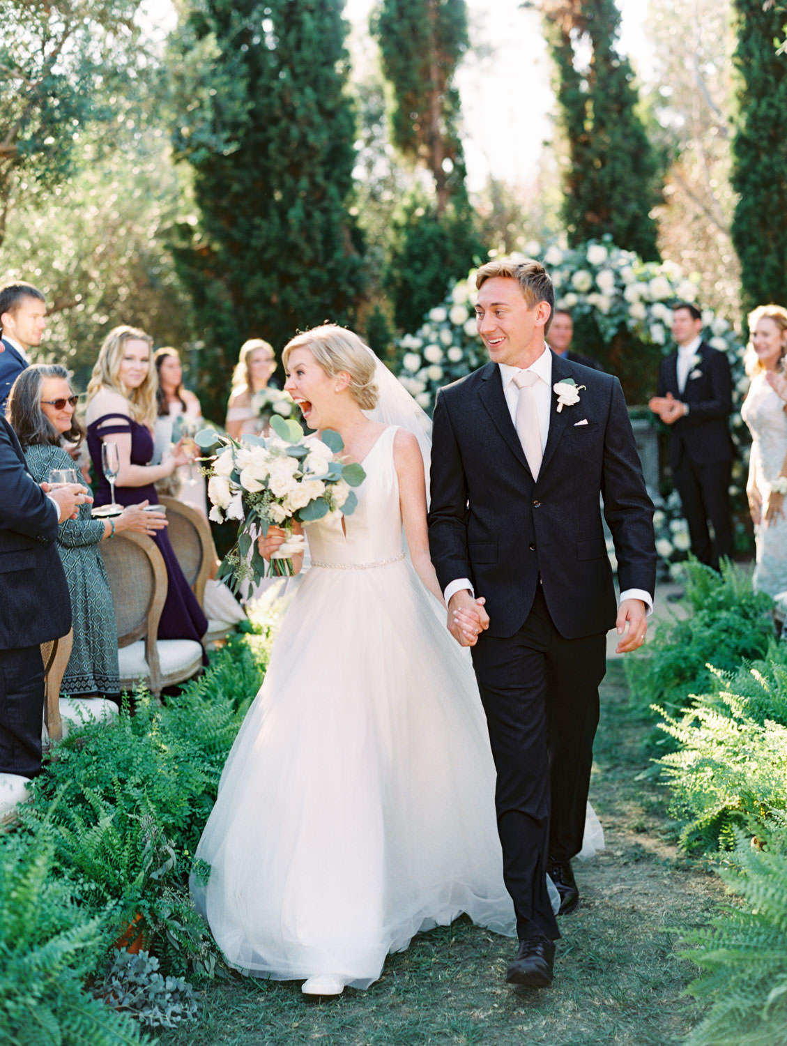 Bride walking up the aisle after the ceremony. Circular ceremony arch with silver dollar eucalyptus, white dahlias and roses. Olive Lawn ceremony with cane back Louis chairs and ferns along the aisle. Estancia La Jolla wedding shot on film by Cavin Elizabeth Photography