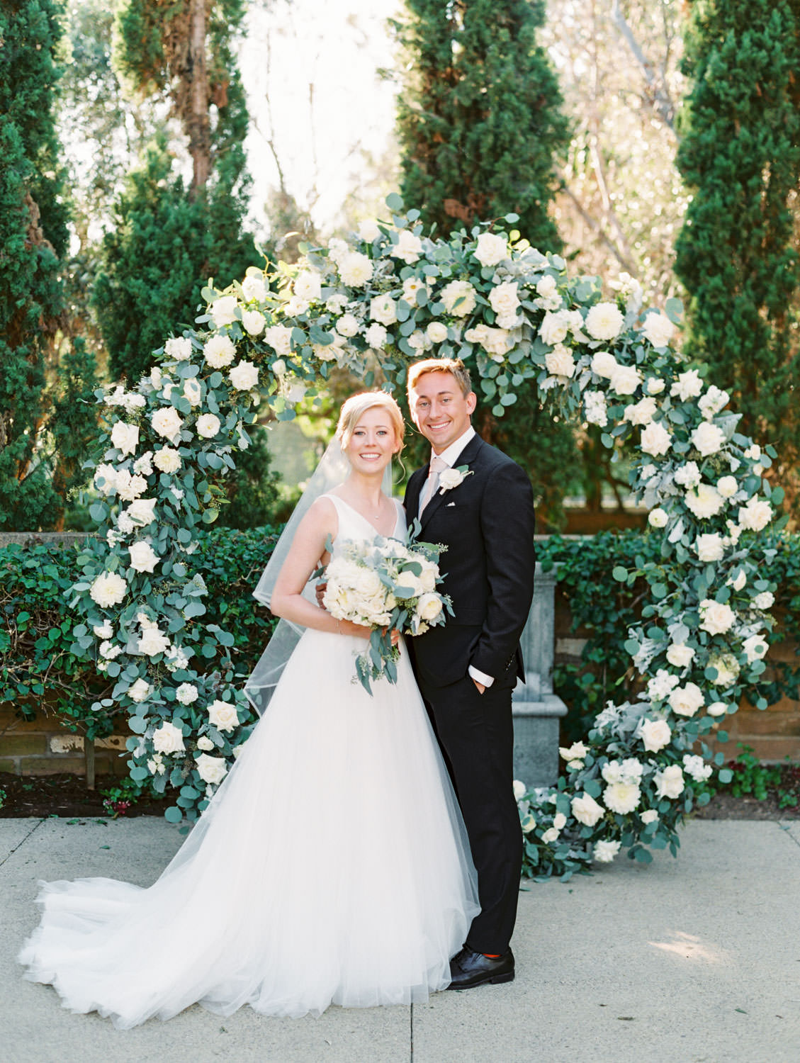 Bride and groom smiling at the camera. Circular ceremony arch with silver dollar eucalyptus, white dahlias and roses. Estancia La Jolla wedding shot on film by Cavin Elizabeth Photography