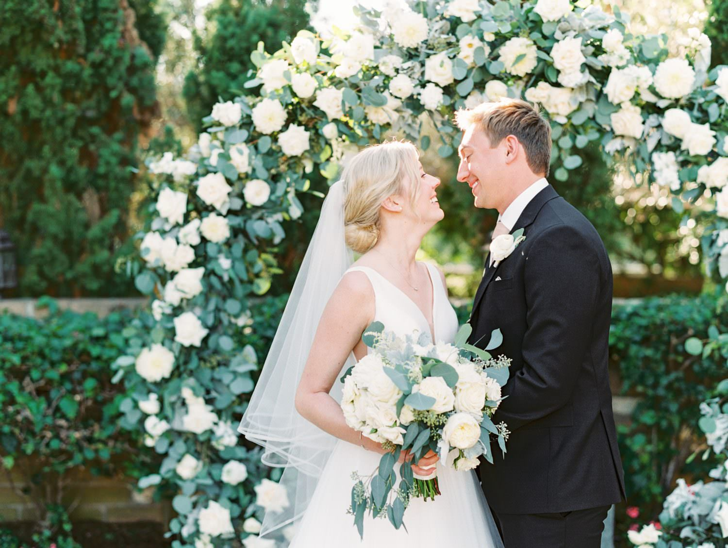 Bride and groom smiling at each other. Bride's hair in low bun with veil. Circular ceremony arch with silver dollar eucalyptus, white dahlias and roses. Estancia La Jolla wedding shot on film by Cavin Elizabeth Photography