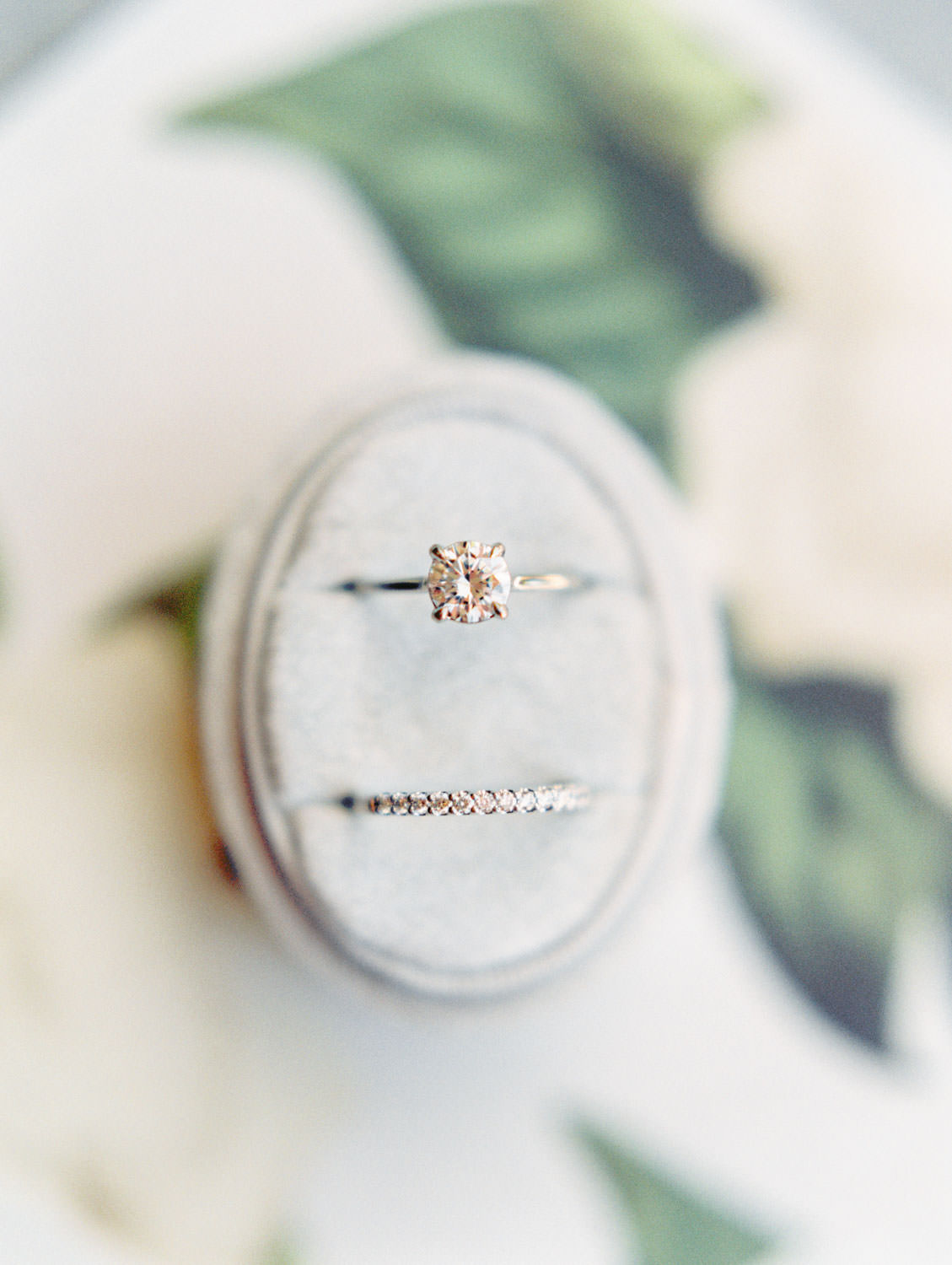 Bride's round solitaire engagement ring and pave band in oval velvet ring box on top of floral envelope liner. Estancia La Jolla wedding shot on film by Cavin Elizabeth Photography. Estancia La Jolla wedding shot on film by Cavin Elizabeth Photography