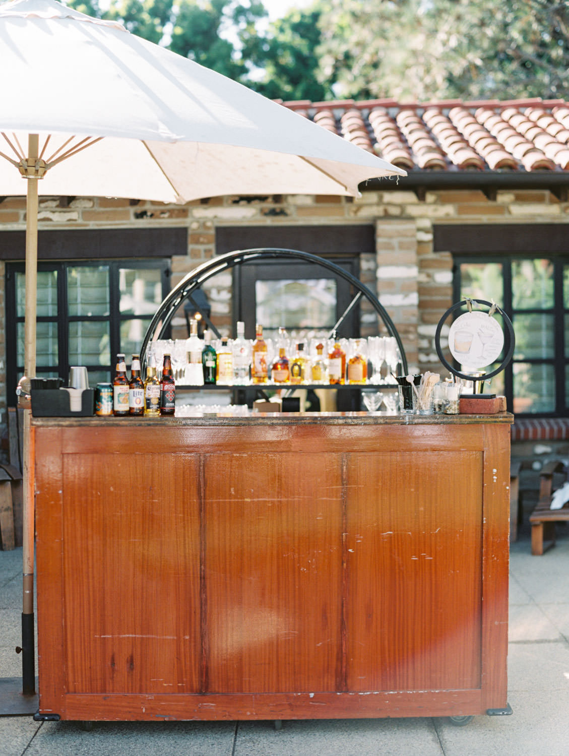 Croquet lawn cocktail hour wooden bar with custom cocktail sign. Shot on film by Cavin Elizabeth.