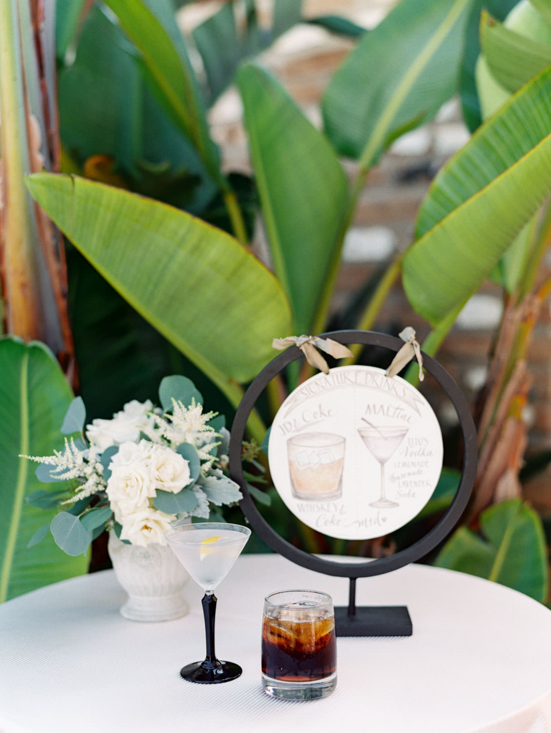 Round suspended cocktail menu color pencil sketch with the real life drinks in front. Whiskey and coke and lemonade martini with lavender. Estancia La Jolla wedding shot on film by Cavin Elizabeth Photography