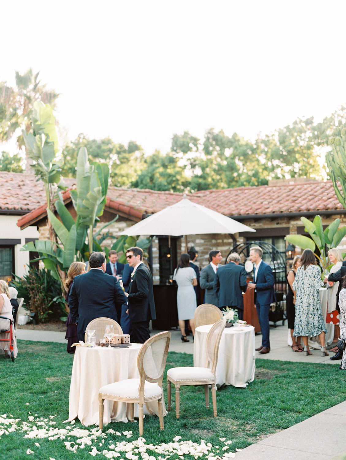Elegant cocktail hour on a croquet lawn with cane back Oak Louis chairs and tables draped in ivory linens. Estancia La Jolla wedding shot on film by Cavin Elizabeth Photography