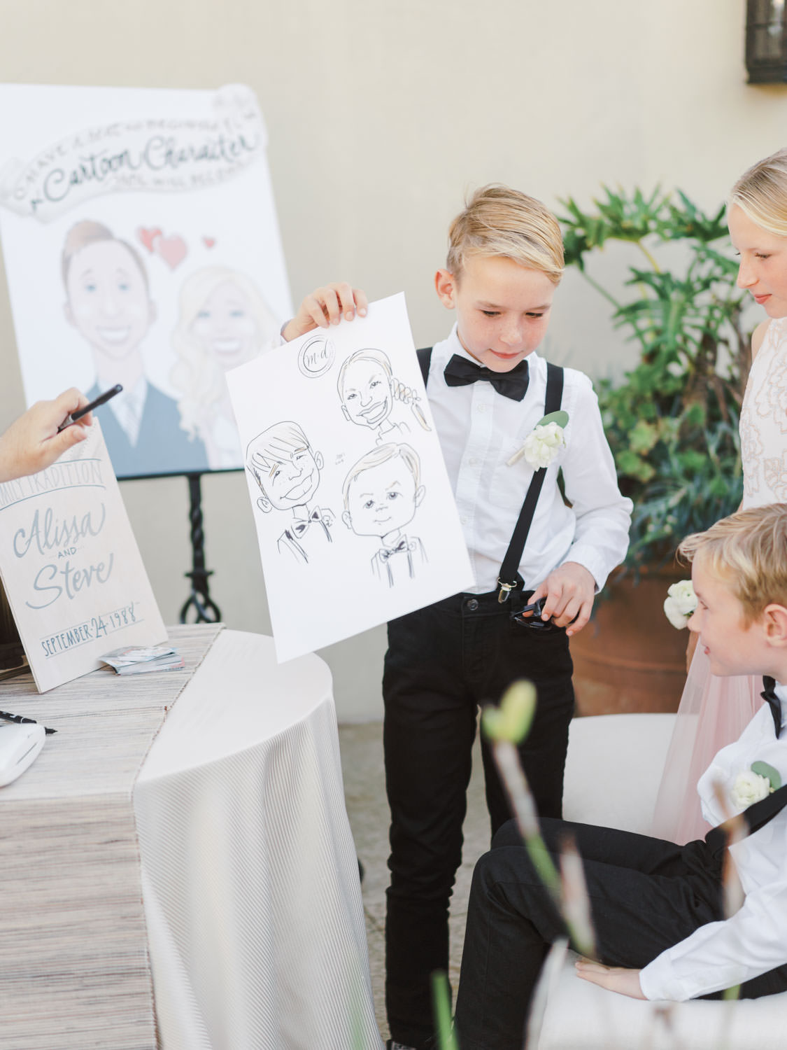 Children at wedding having caricatures drawn of themselves. Estancia La Jolla wedding shot on film by Cavin Elizabeth Photography