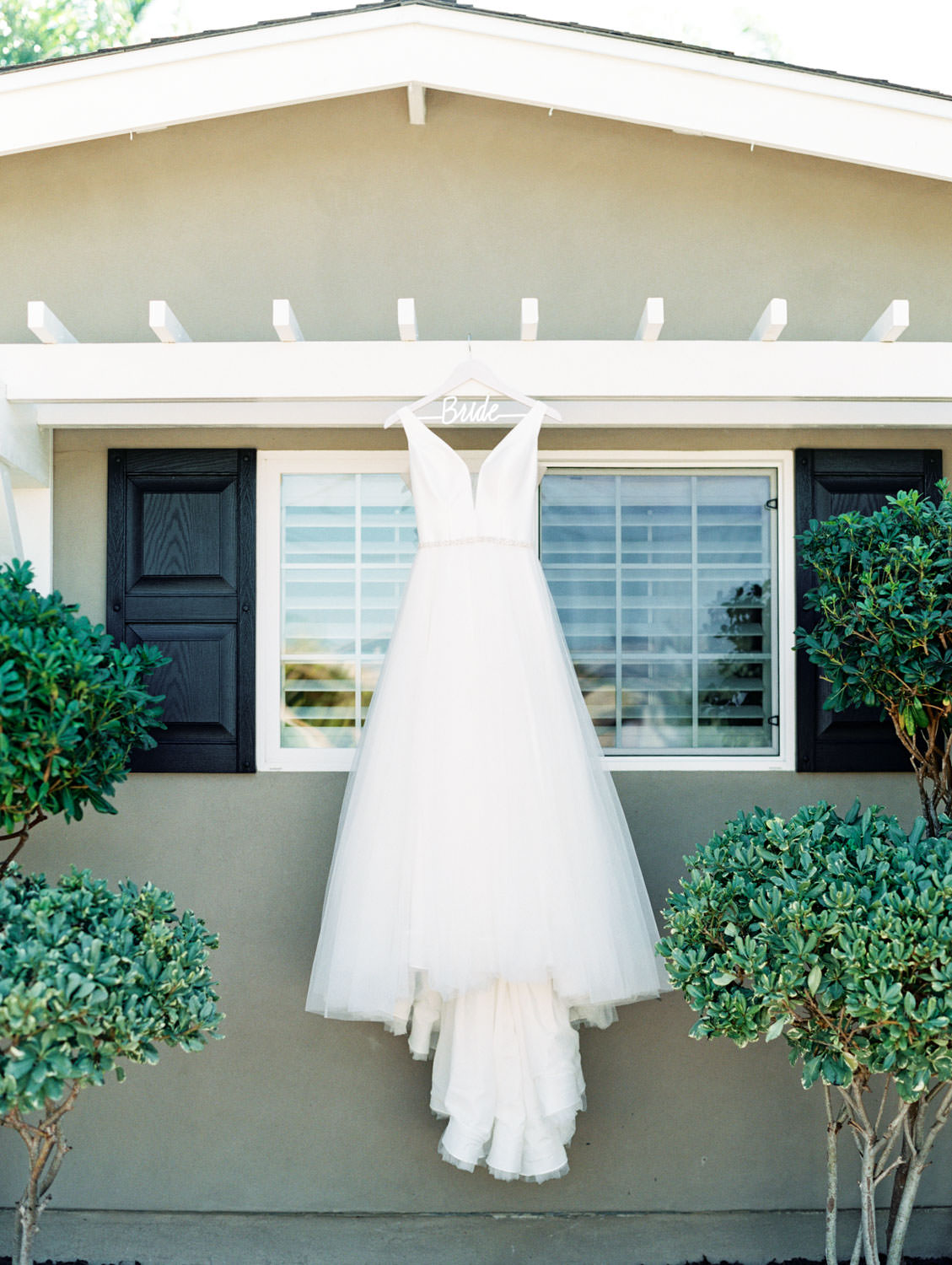 Bride's gown from Stella York hanging outside her home. Estancia La Jolla wedding shot on film by Cavin Elizabeth Photography. La Jolla wedding shot on film by Cavin Elizabeth Photography