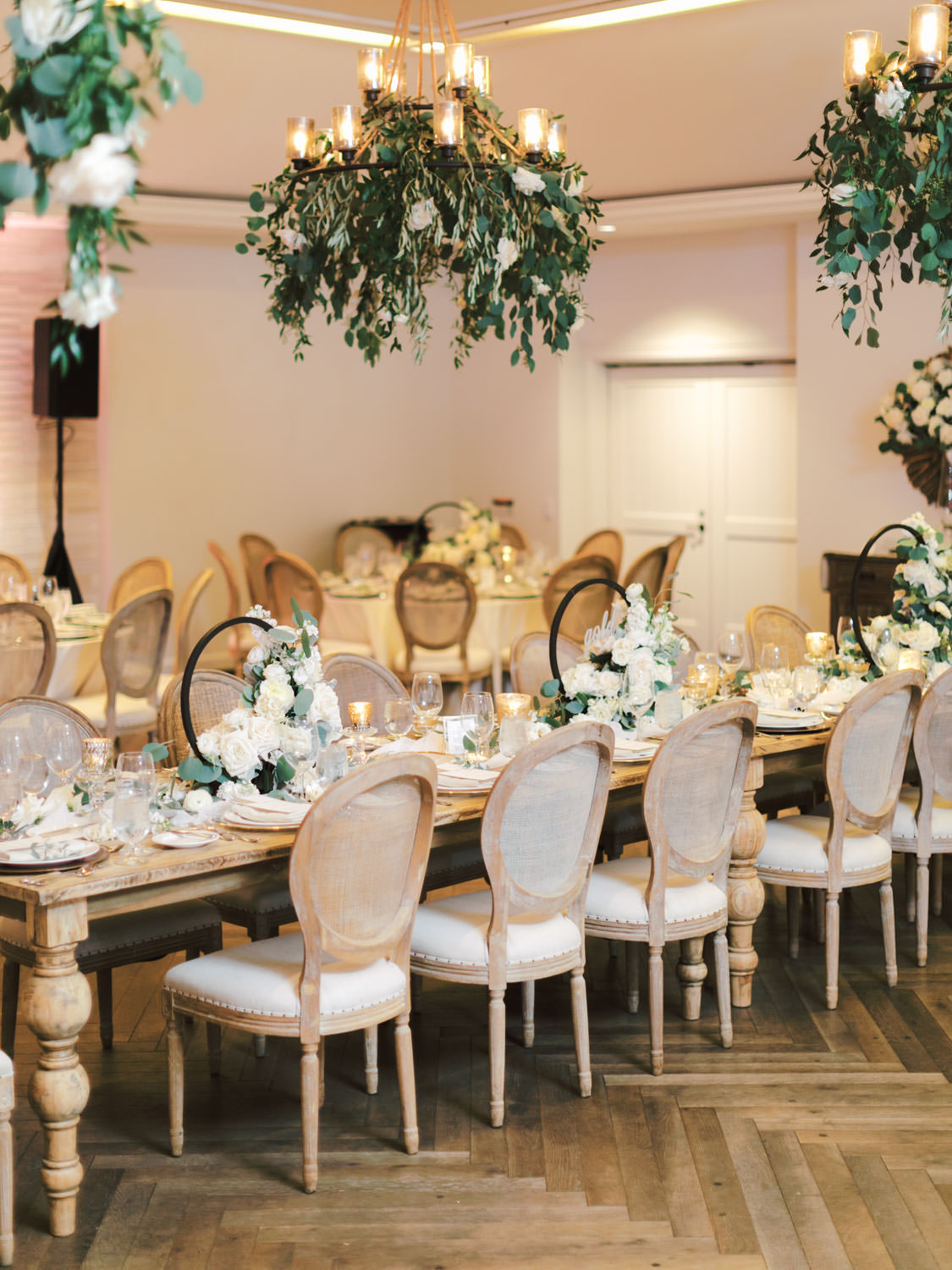 Cane back Oak Louis chairs surrounding a long natural wood farm table topped with green and ivory centerpieces built around a black metal hoop. Chandeliers with hanging greenery and roses. Estancia La Jolla Grande Room reception by Cavin Elizabeth Photography