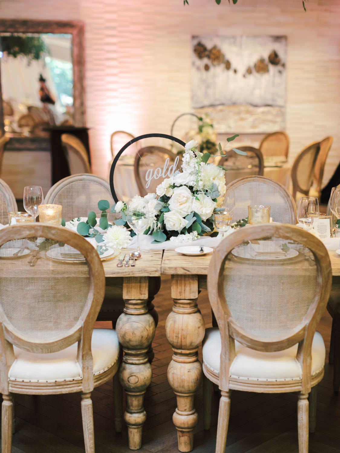 Cane back Oak Louis chairs surrounding a long natural wood farm table topped with green and ivory centerpieces built around a black metal hoop. Estancia La Jolla Grande Room reception by Cavin Elizabeth Photography