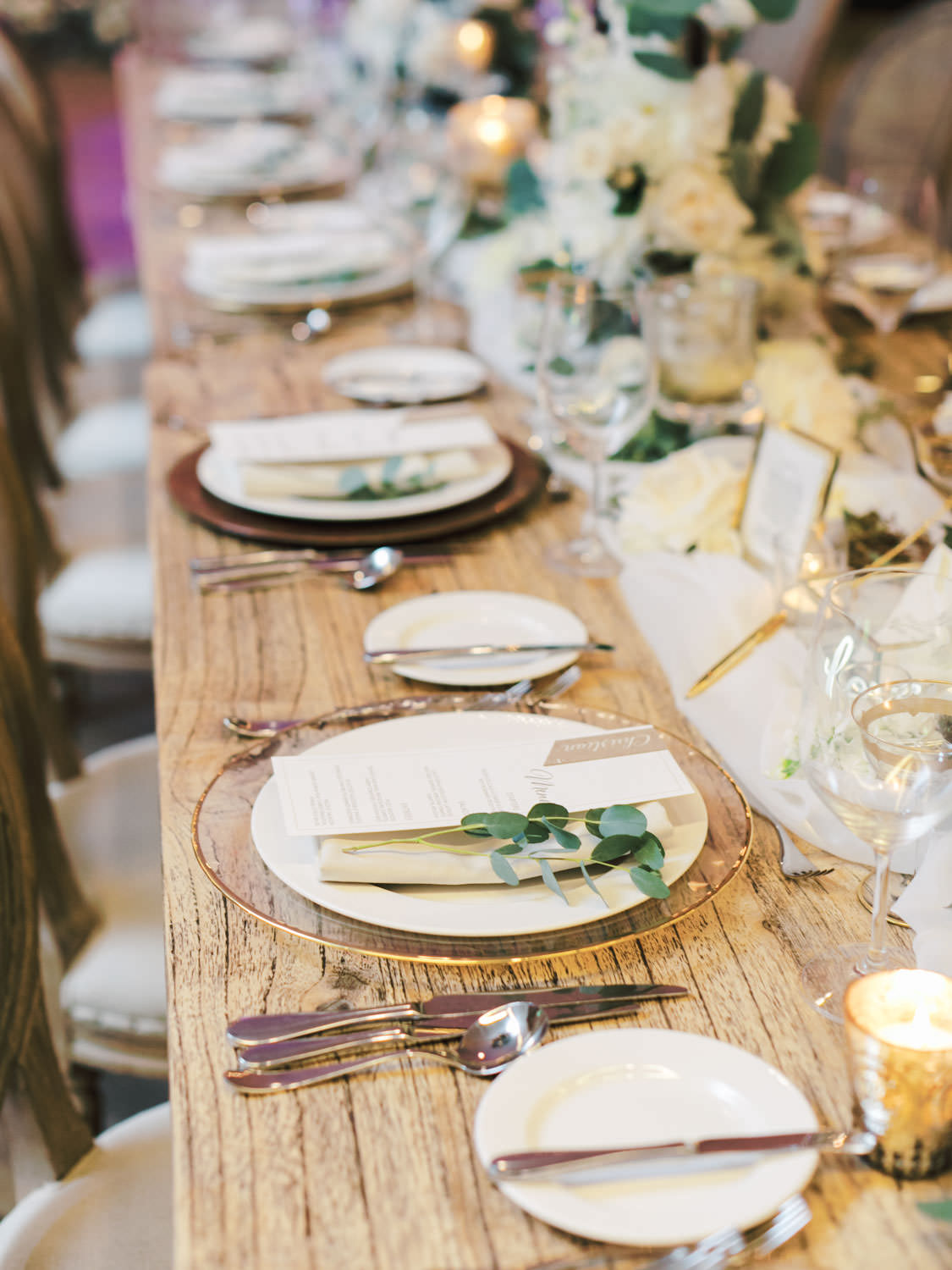 Clear chargers with gold rim and ivory places topped with ivory napkin and menu with eucalyptus sprig on a long natural wood farm table topped with green and ivory centerpieces built around a black metal hoop. Estancia La Jolla Grande Room reception by Cavin Elizabeth Photography