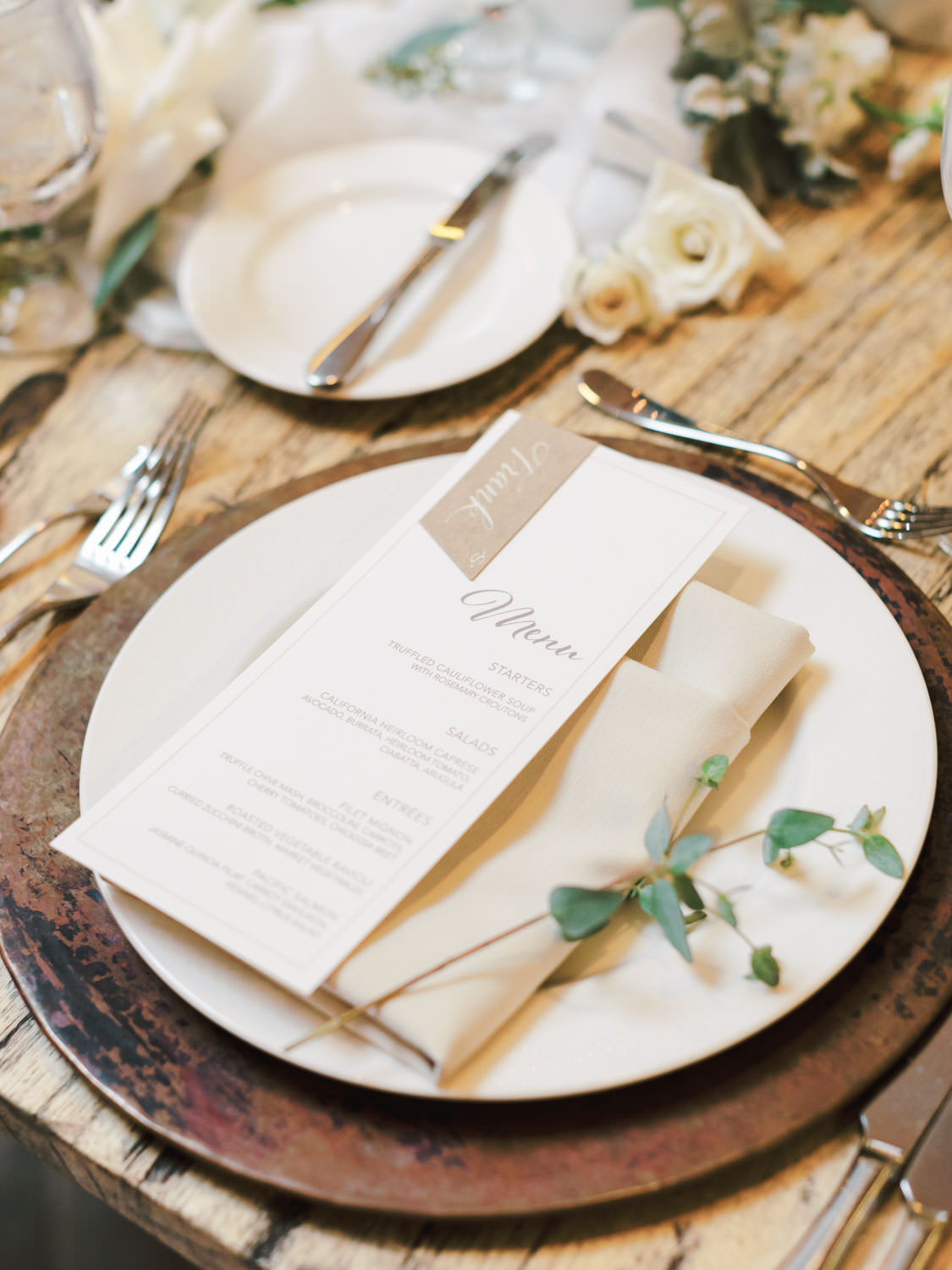 Worn metal chargers and ivory places topped with ivory napkin and menu with eucalyptus sprig on a long natural wood farm table topped with green and ivory centerpieces built around a black metal hoop. Estancia La Jolla Grande Room reception by Cavin Elizabeth Photography