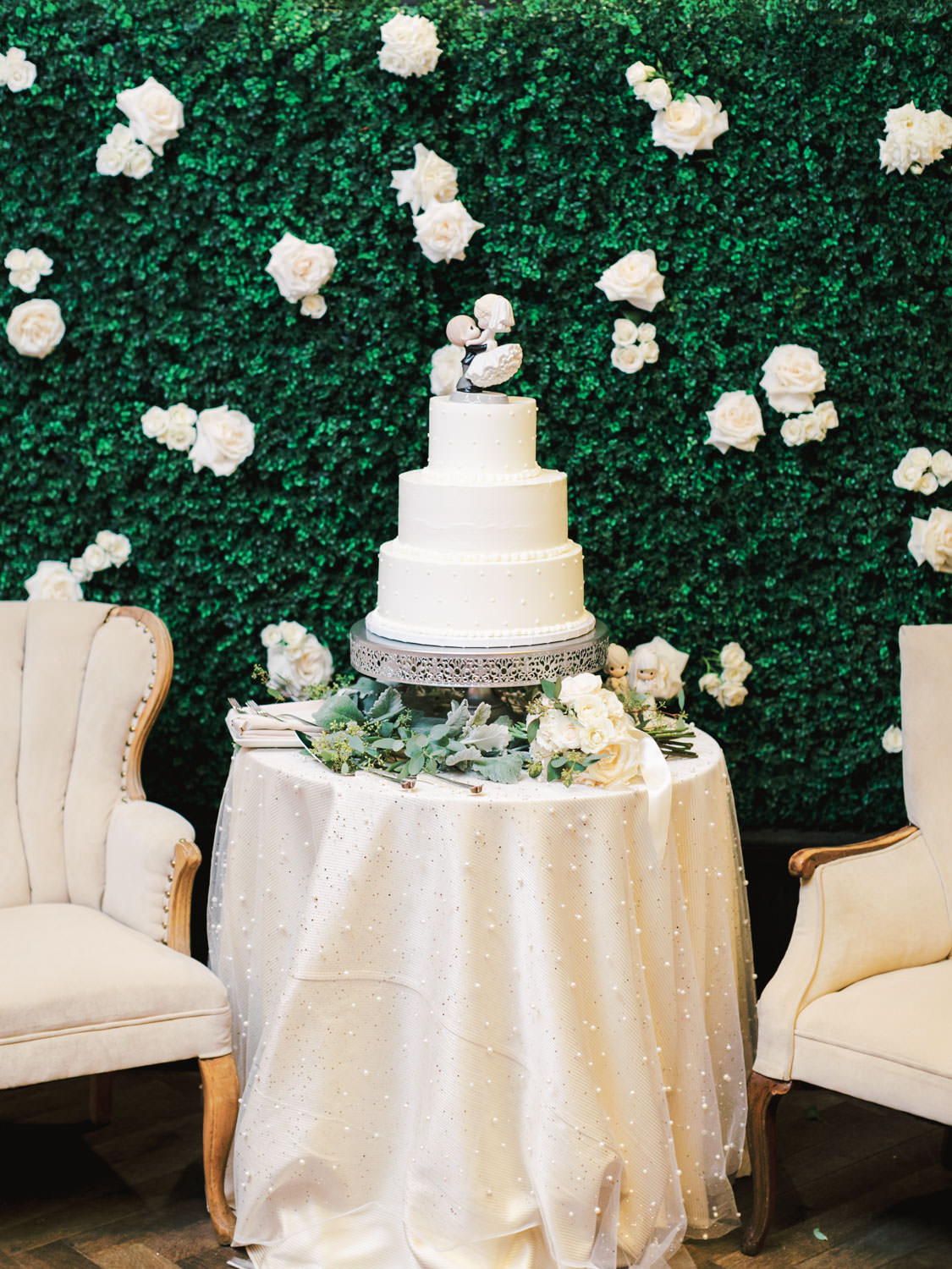 Ivory pearl linen on a cake table. three tier ivory buttercream cake topped with porcelain doll figurine in front of a greenery hedge backdrop. Estancia La Jolla Grande Room reception by Cavin Elizabeth Photography
