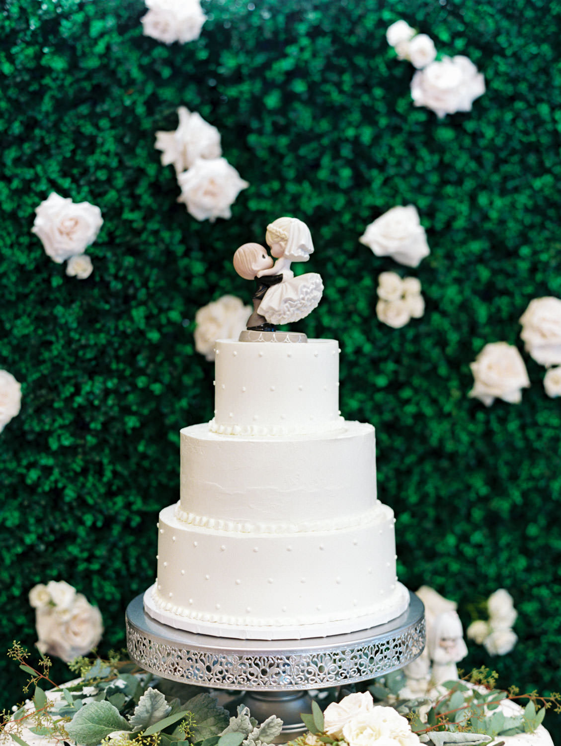 three tier ivory buttercream cake topped with porcelain doll figurine in front of a greenery hedge backdrop. Estancia La Jolla Grande Room reception by Cavin Elizabeth Photography