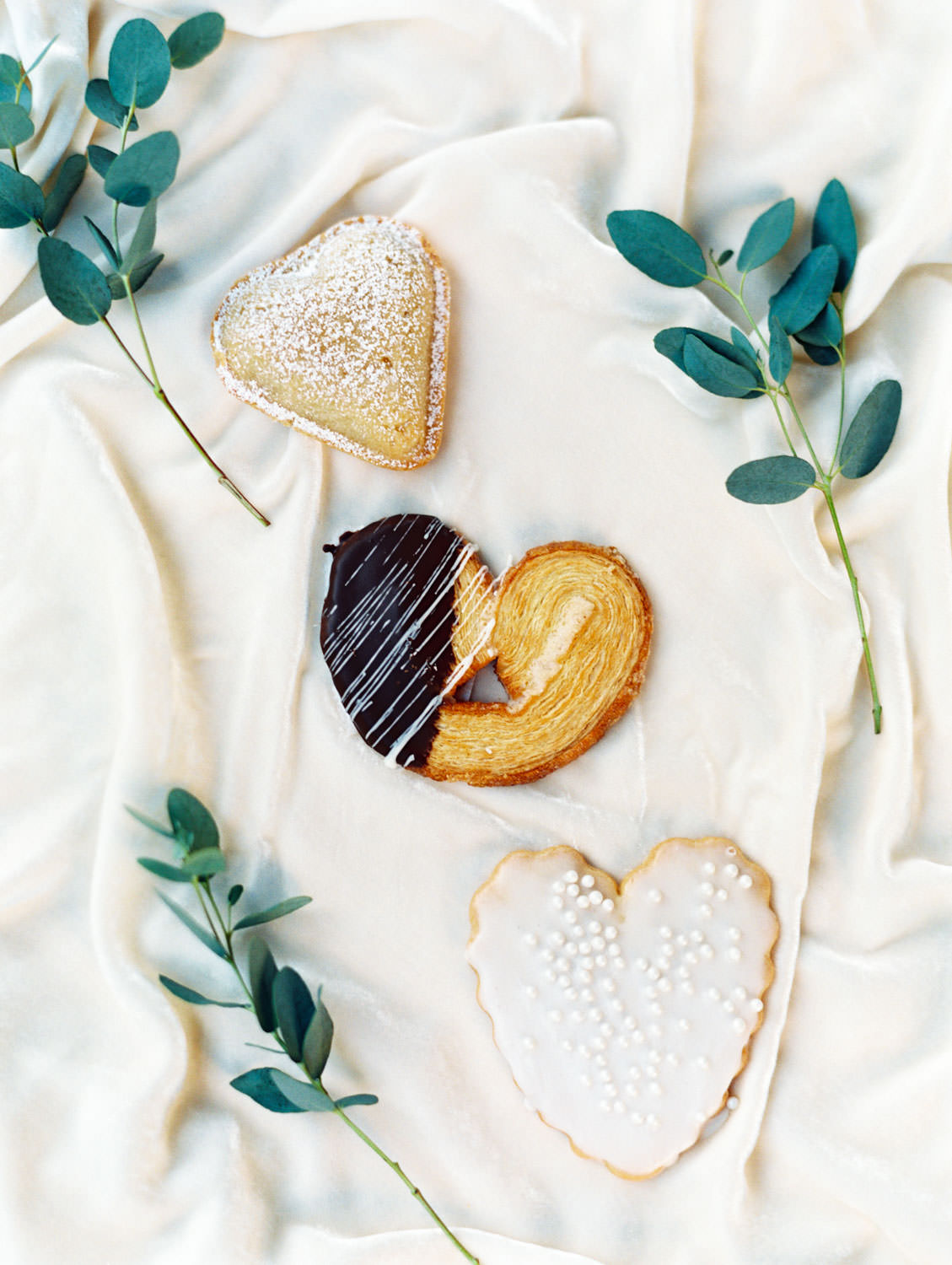 Wedding dessert flatlay with eucalyptus and heart shaped cookies: powdered sugar, chocolate dipped, and icing with pearls. Cavin Elizabeth Photography