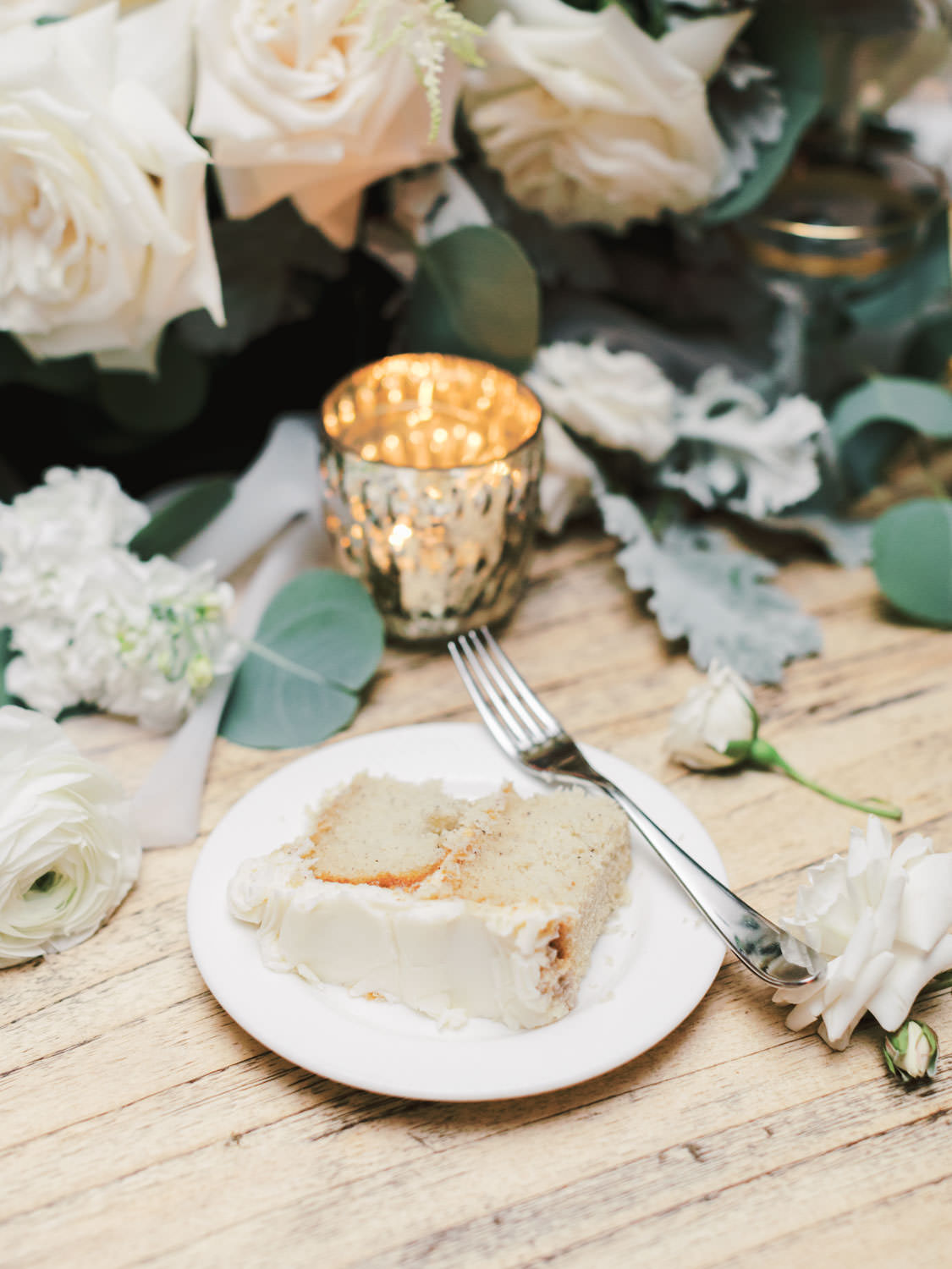 Slice of banana cake with cream cheese icing on a long natural wood farm table topped with green and ivory centerpieces built around a black metal hoop. Estancia La Jolla Grande Room reception by Cavin Elizabeth Photography