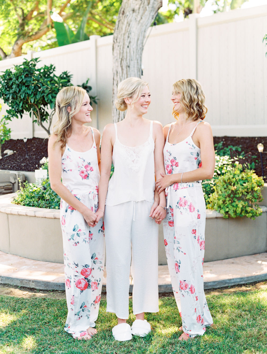 Bride in white silk pajamas with bridesmaids in floral pajamas. Estancia La Jolla wedding shot on film by Cavin Elizabeth Photography. Estancia La Jolla wedding shot on film by Cavin Elizabeth Photography