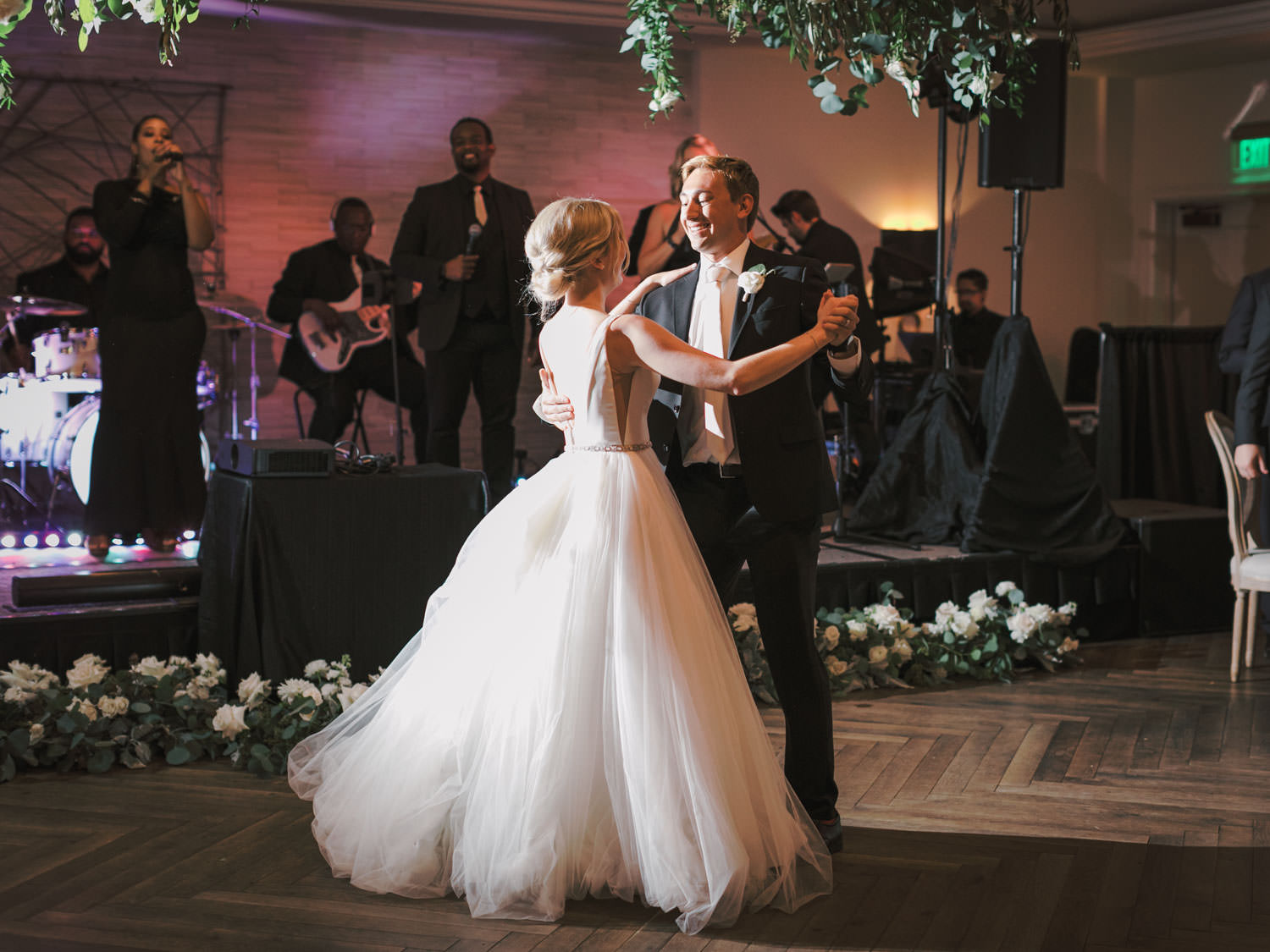Bride and groom first dance in front of band stage lined with ivory and green centerpieces. Estancia La Jolla Grande Room reception by Cavin Elizabeth Photography