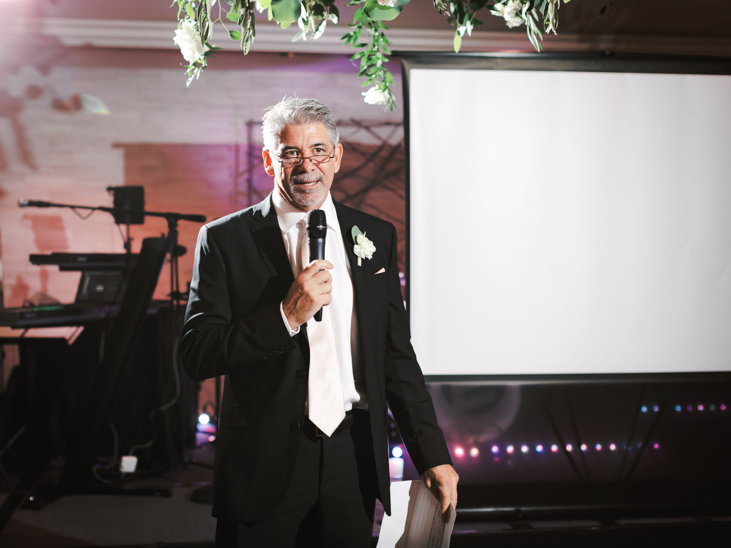Father of the bride toast in front of band stage lined with ivory and green centerpieces. Estancia La Jolla Grande Room reception by Cavin Elizabeth Photography