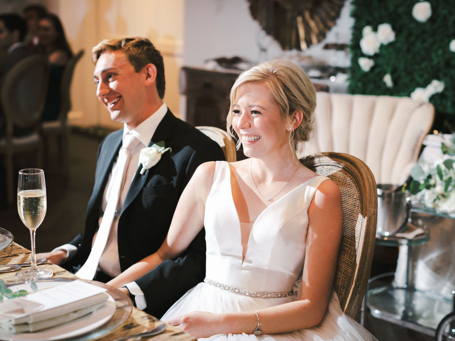 Bride and groom reacting to wedding toasts. Estancia La Jolla Grande Room reception by Cavin Elizabeth Photography