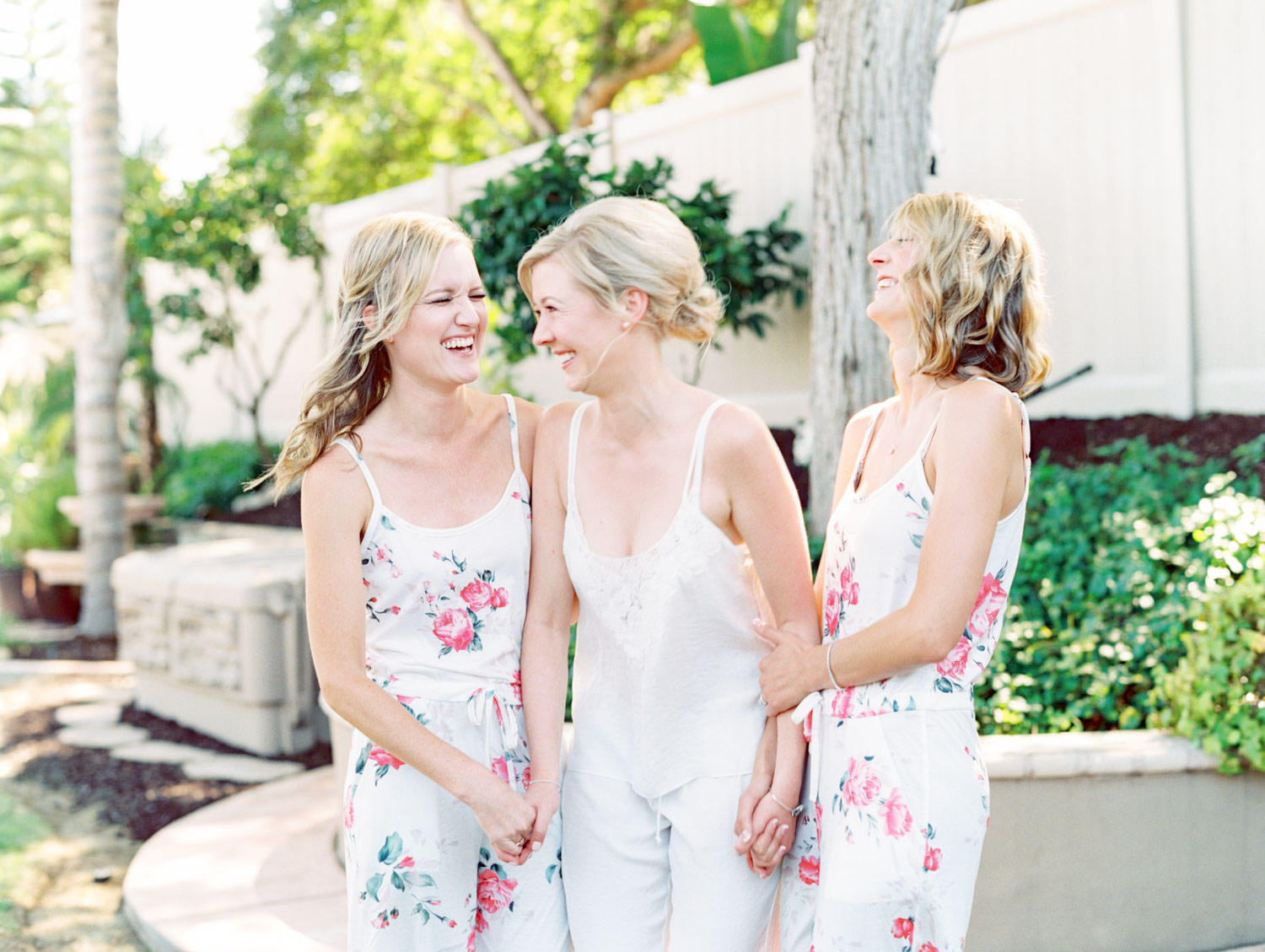 Bride in white silk pajamas laughing with bridesmaids in floral pajamas. Estancia La Jolla wedding shot on film by Cavin Elizabeth Photography. Estancia La Jolla wedding shot on film by Cavin Elizabeth Photography
