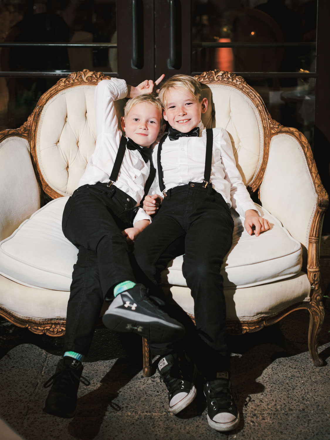 Ring bearers lounging on a sofa at the end of the wedding. Estancia La Jolla Grande Room reception by Cavin Elizabeth Photography