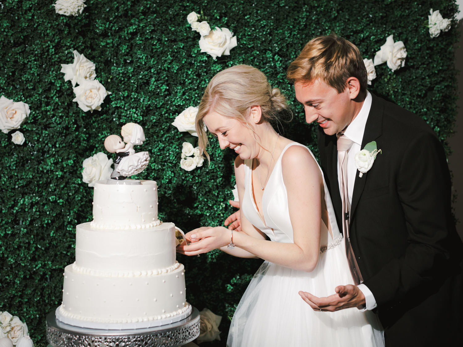 Bride and groom cutting their three tier ivory buttercream cake topped with porcelain doll figurine in front of a greenery hedge backdrop. Estancia La Jolla Grande Room reception by Cavin Elizabeth Photography