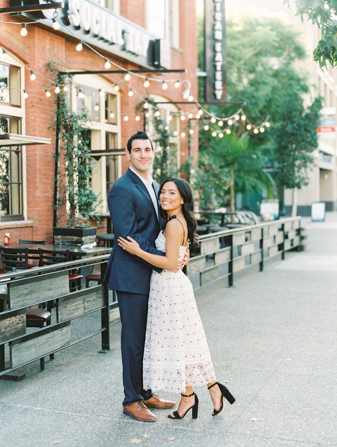 Groom and bride at a smiling at the camera. Bride in self portrait Ivory Hibiscus Floral Guipure Midi Dress and groom in navy suit. Downtown San Diego engagement photos on film by Cavin Elizabeth Photography