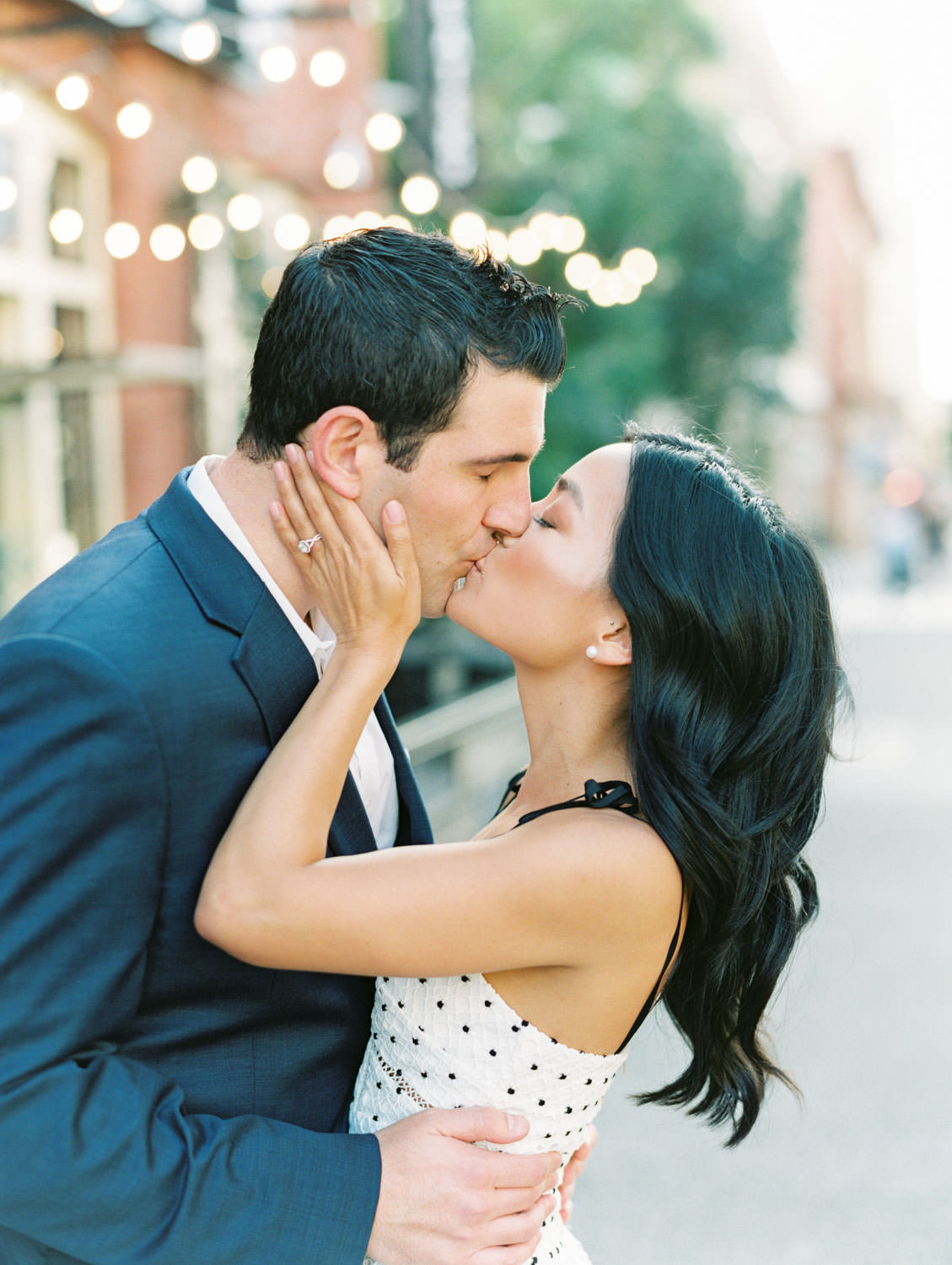 Groom and bride at a kissing. Bride in self portrait Ivory Hibiscus Floral Guipure Midi Dress and groom in navy suit. Downtown San Diego engagement photos on film by Cavin Elizabeth Photography