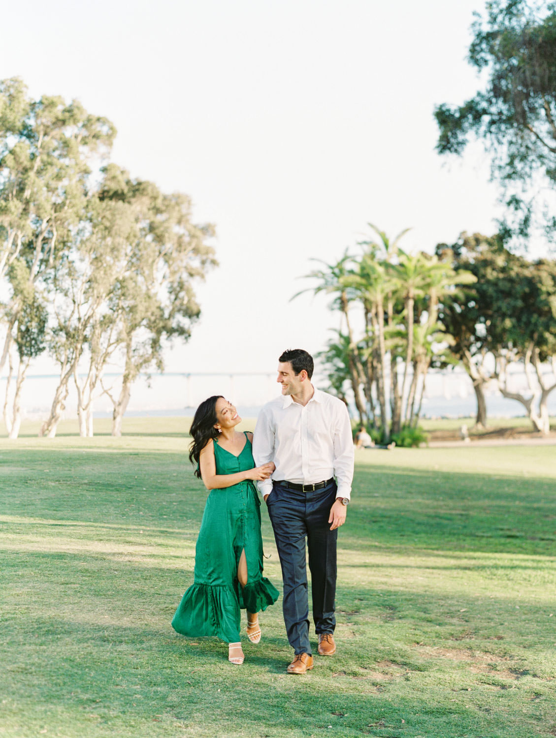 Groom and bride walking. Bride in Tularosa Villa Dress from Revolve and groom in white button down and . San Diego Embarcadero North engagement photos on film by Cavin Elizabeth Photography