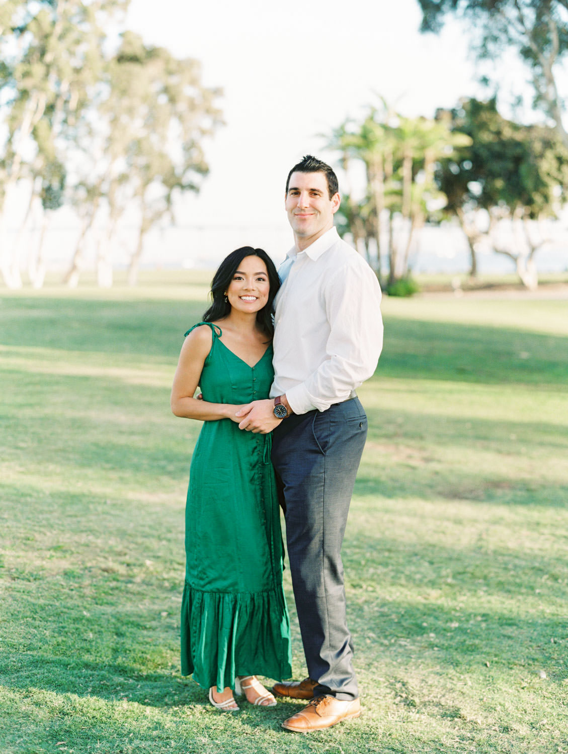 Groom and bride smiling at the camera. Bride in Tularosa Villa Dress from Revolve and groom in white button down and . San Diego Embarcadero North engagement photos on film by Cavin Elizabeth Photography