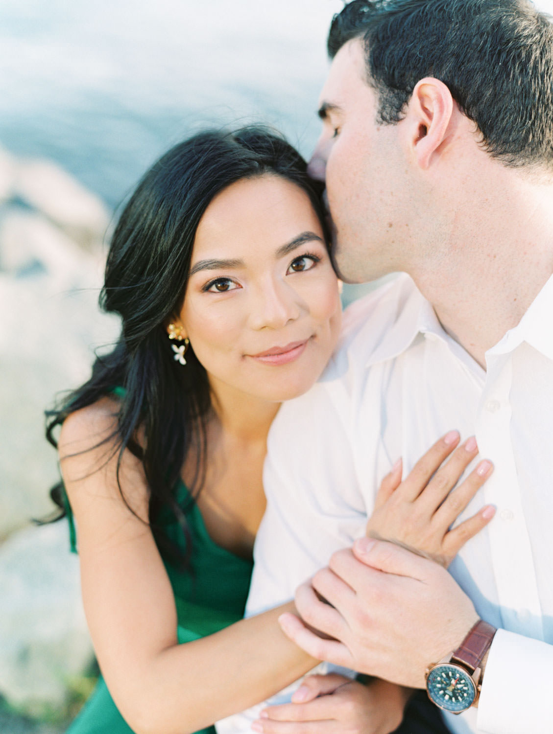 Bride looking at the camera while groom kisses her head. Bride in Tularosa Villa Dress from Revolve and groom in white button down and . San Diego Embarcadero North engagement photos on film by Cavin Elizabeth Photography