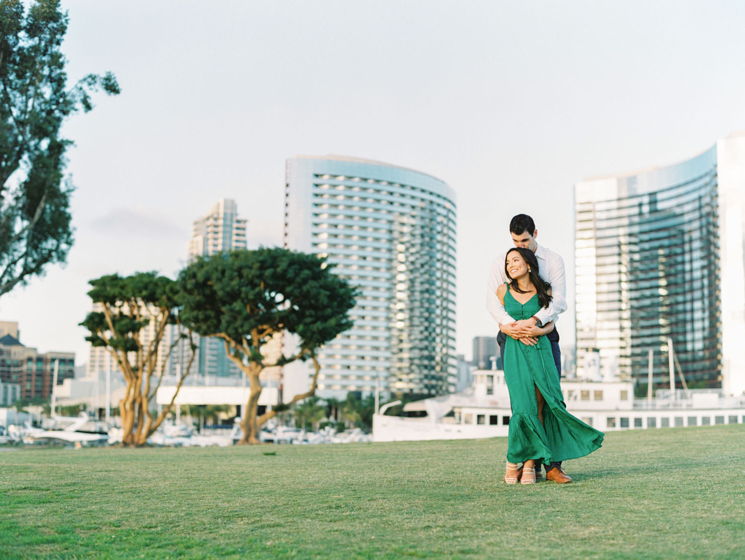 Groom and bride hugging with the city skyline behind them. Bride in Tularosa Villa Dress from Revolve and groom in white button down and . San Diego Embarcadero North engagement photos on film by Cavin Elizabeth Photography