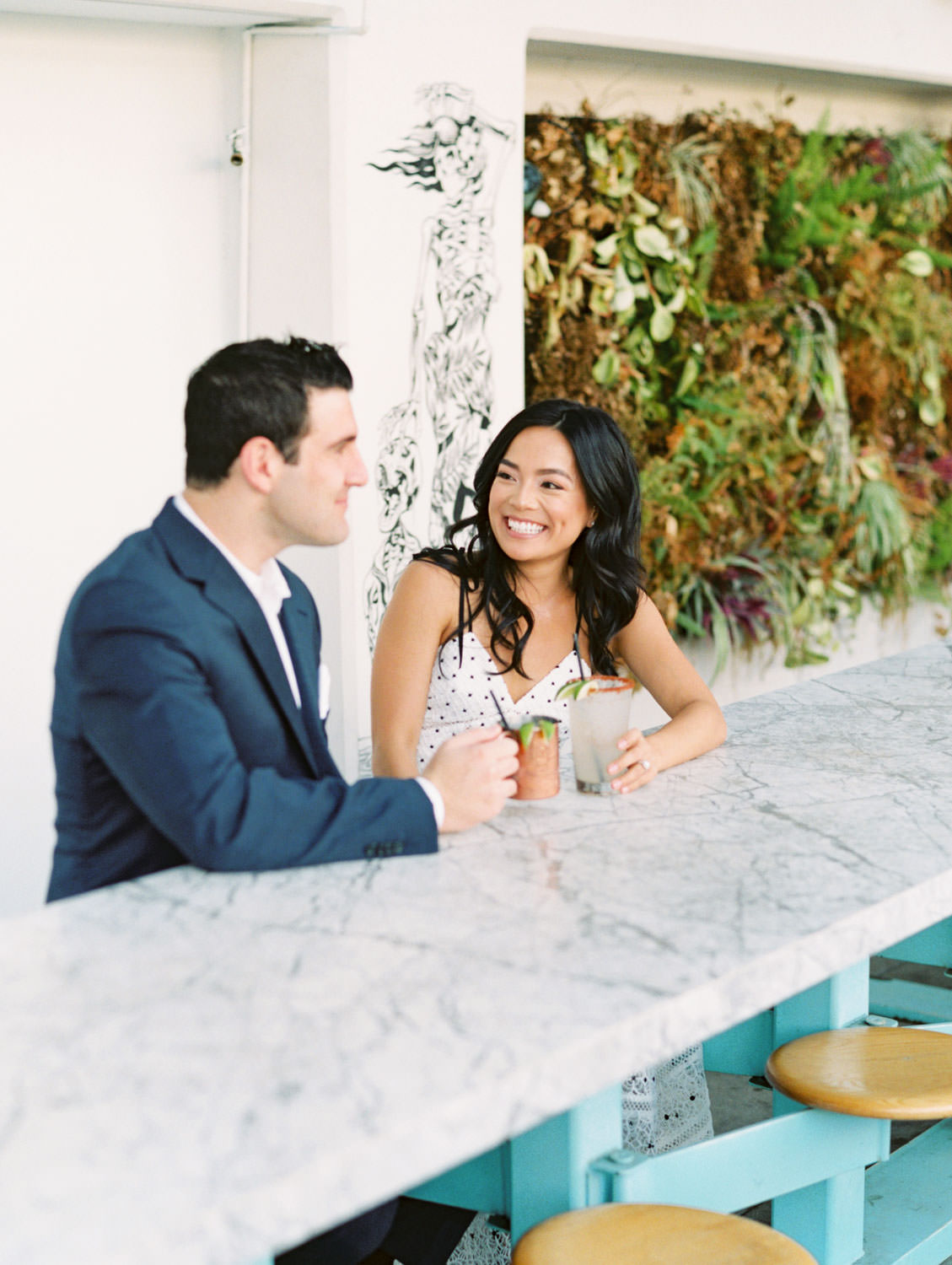 Groom and bride at a marble table drinking cocktails and laughing. Fairweather Rooftop Bar Engagement Photos on film by Cavin Elizabeth Photography