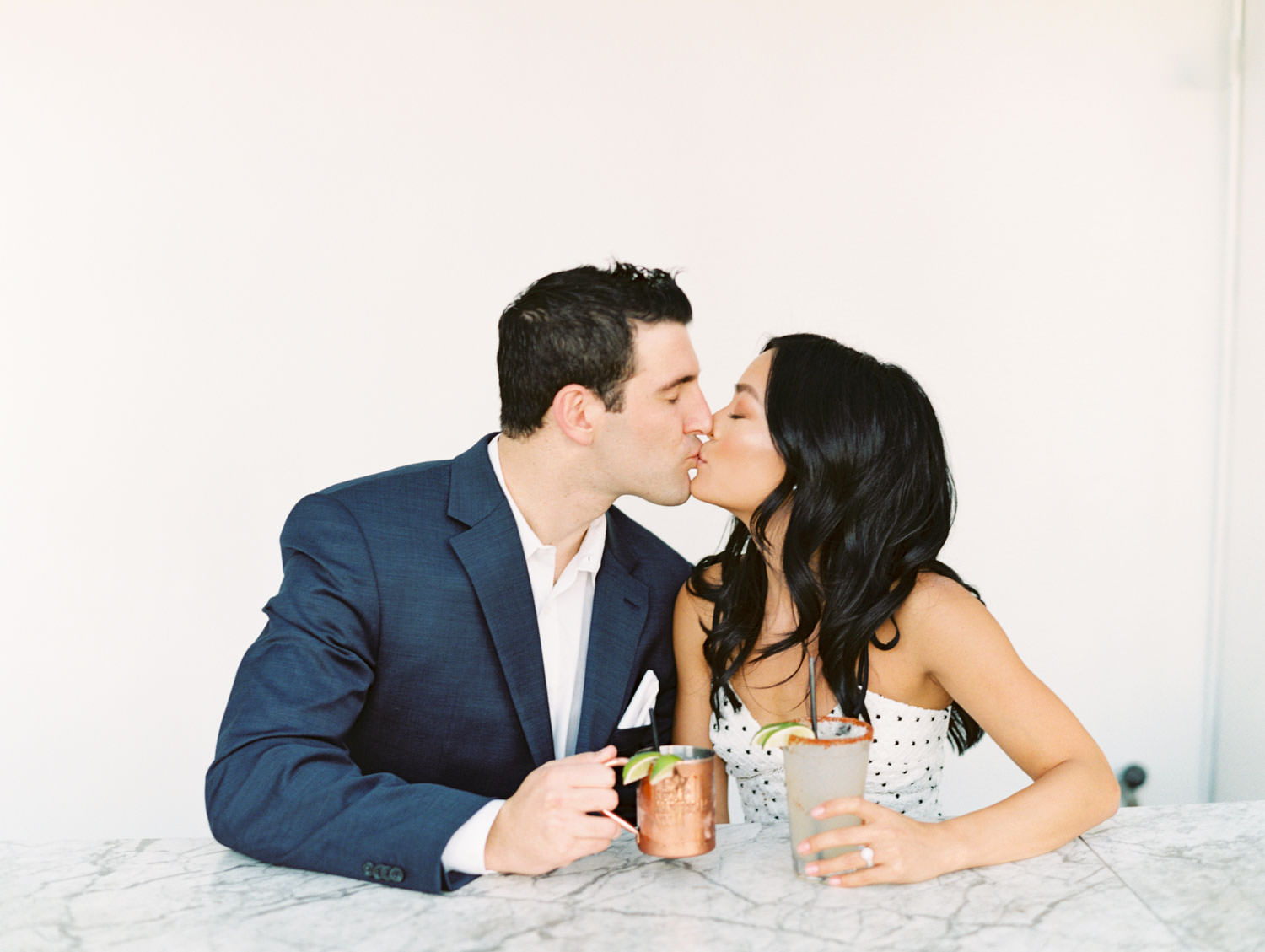 Groom and bride at a marble table drinking cocktails and kissing. Fairweather Rooftop Bar Engagement Photos on film by Cavin Elizabeth Photography