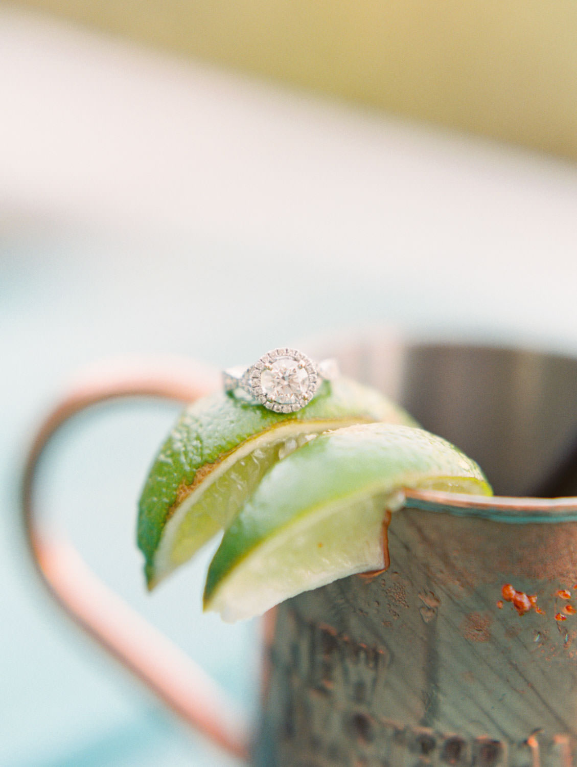 Round engagement ring with halo on top of limes of a mule in a copper mug. Fairweather Rooftop Bar Engagement Photos on film by Cavin Elizabeth Photography