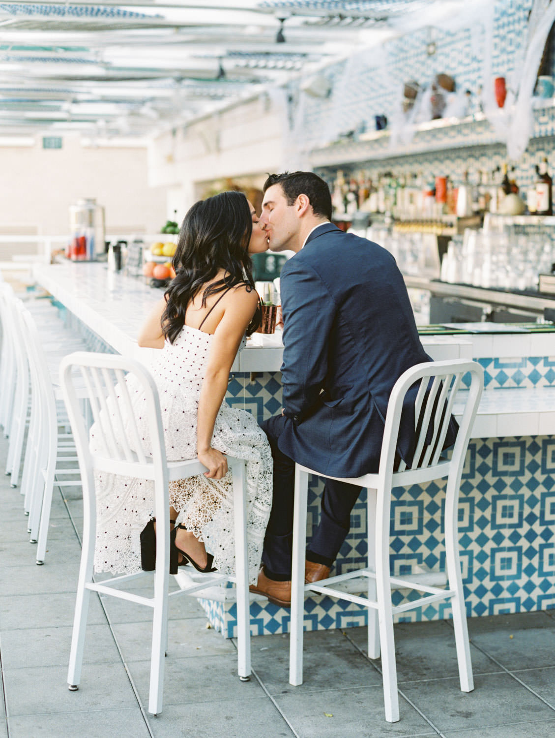 Groom and bride at a marble table drinking cocktails and kissing. Bride in self portrait Ivory Hibiscus Floral Guipure Midi Dress and groom in navy suit. Fairweather Rooftop Bar Engagement Photos on film by Cavin Elizabeth Photography