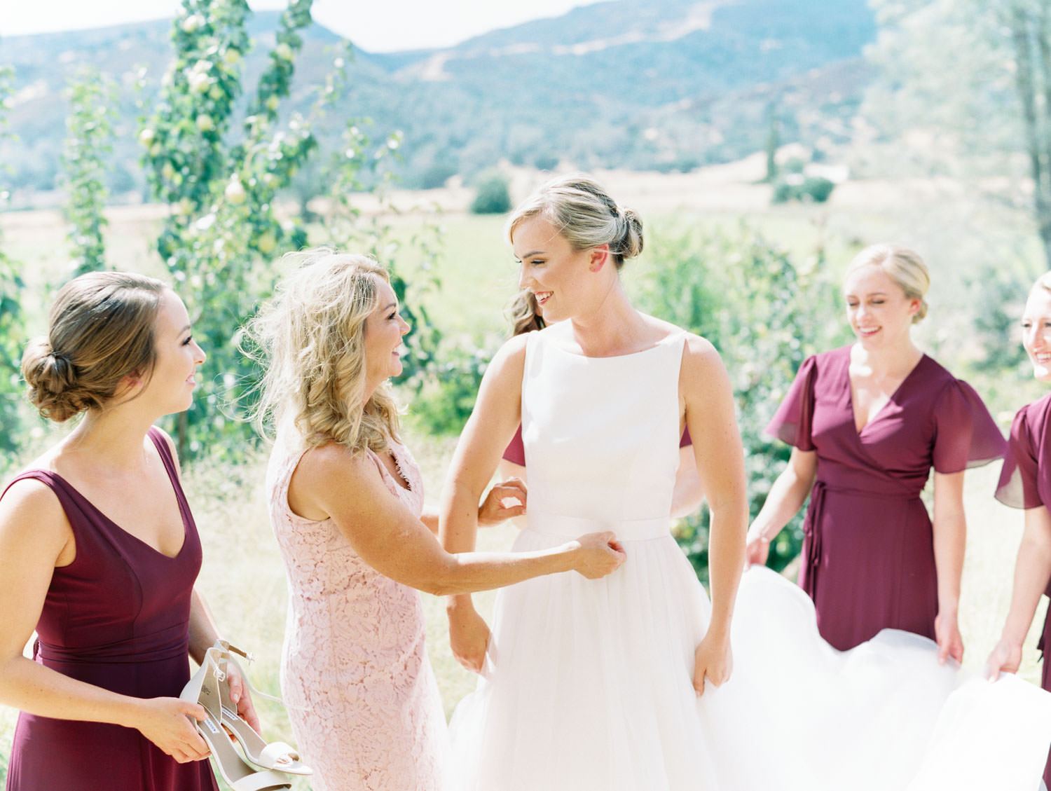 Mother of the bride helping the bride into her classic Mikaella Bridal gown with bridesmaids in deep wine gowns by Show Me Your Mumu. Full Belly Farm on Martha Stewart Weddings by film photographer Cavin Elizabeth Photography