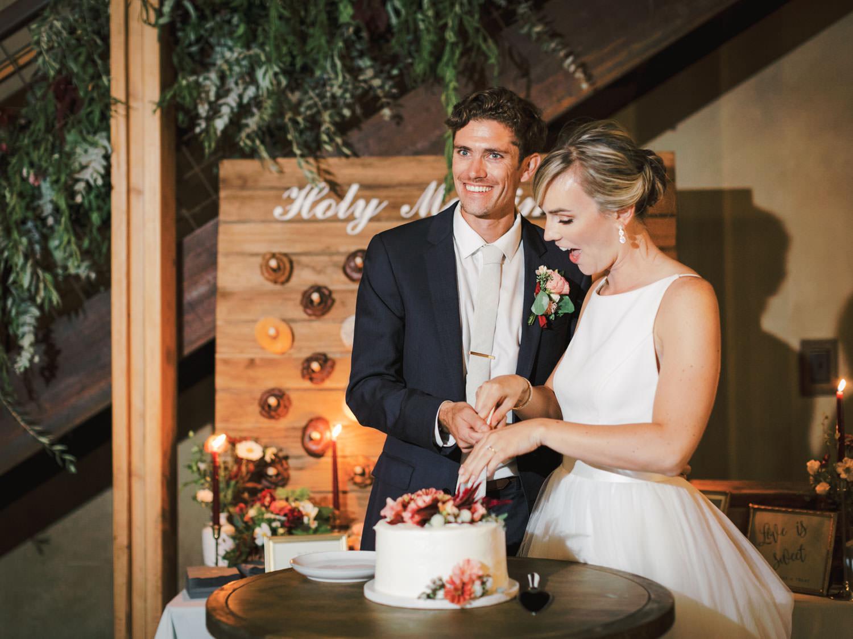 Bride and groom cutting their cake. Full Belly Farm reception by film photographer Cavin Elizabeth Photography
