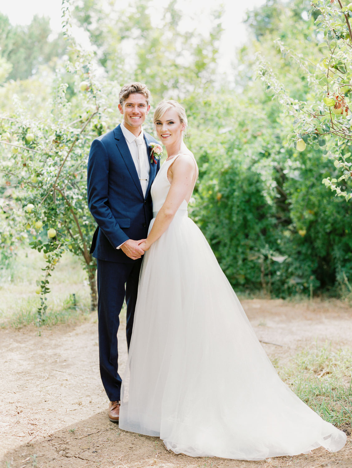 Bride in a classic Mikaella Bridal gown smiling at the camera with the groom in a navy linen suit. Full Belly Farm on Martha Stewart Weddings by film photographer Cavin Elizabeth Photography