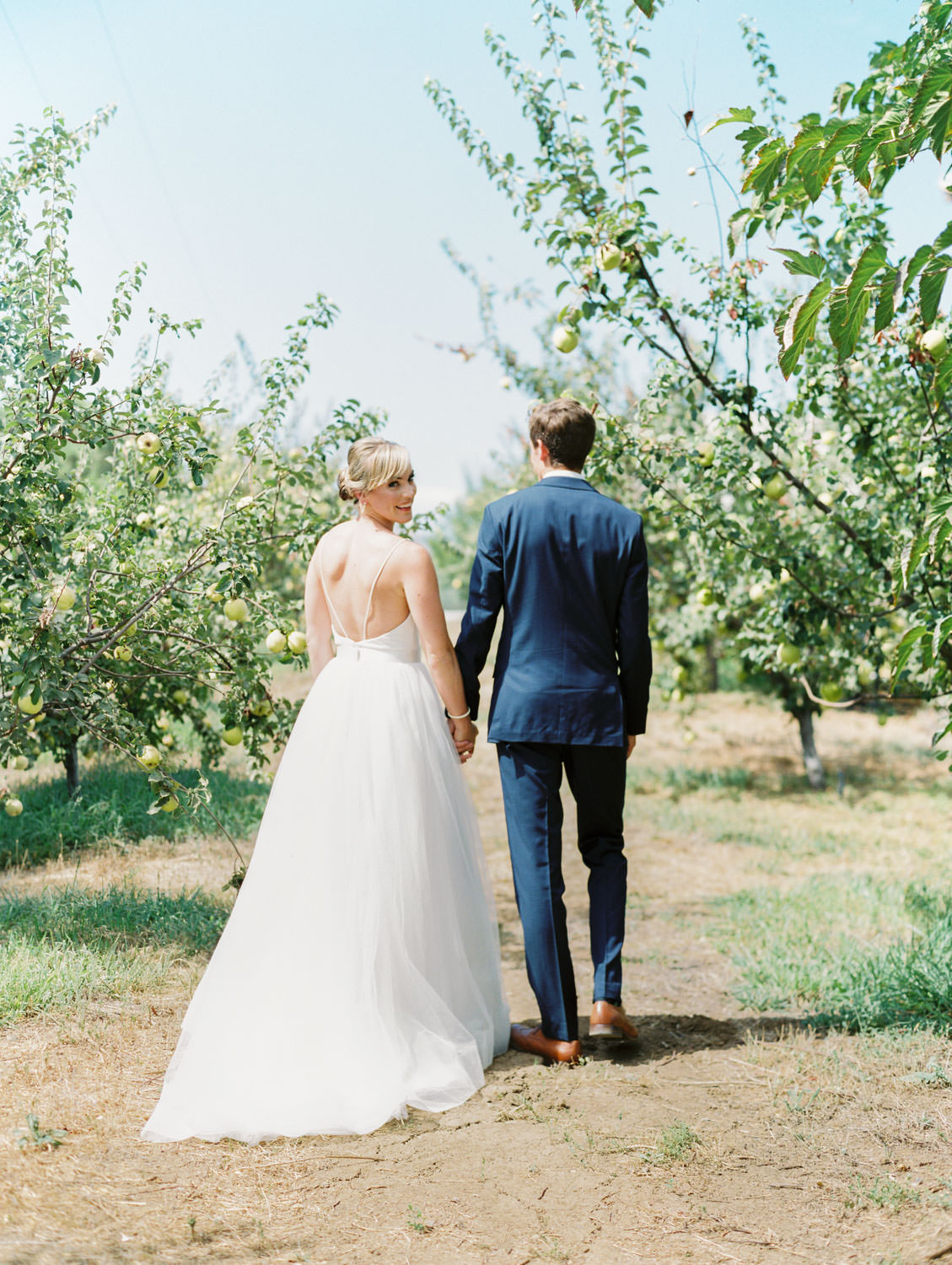 Bride in a classic Mikaella Bridal gown walking with the groom in a navy linen suit. Full Belly Farm on Martha Stewart Weddings by film photographer Cavin Elizabeth Photography