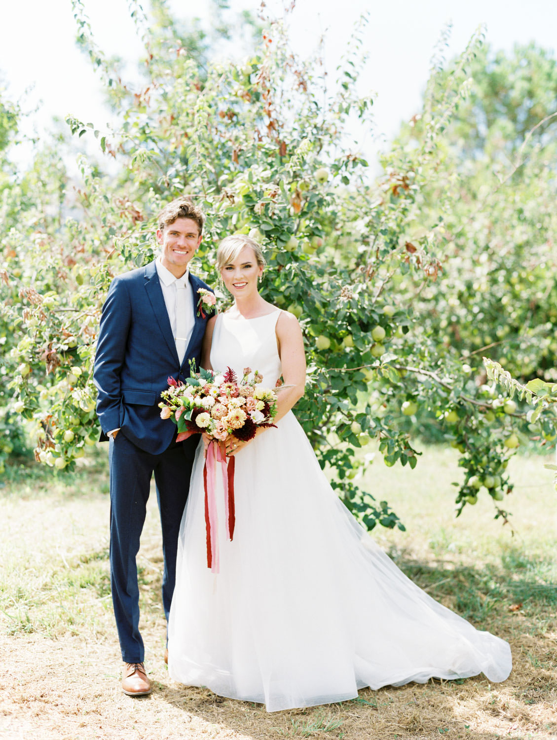 Bride in a classic Mikaella Bridal gown smiling at the camera with the groom in a navy linen suit. Bridal bouquet with ivory, peach, wine, blush flowers and mauve, wine, and blush ribbons. Full Belly Farm on Martha Stewart Weddings by film photographer Cavin Elizabeth Photography