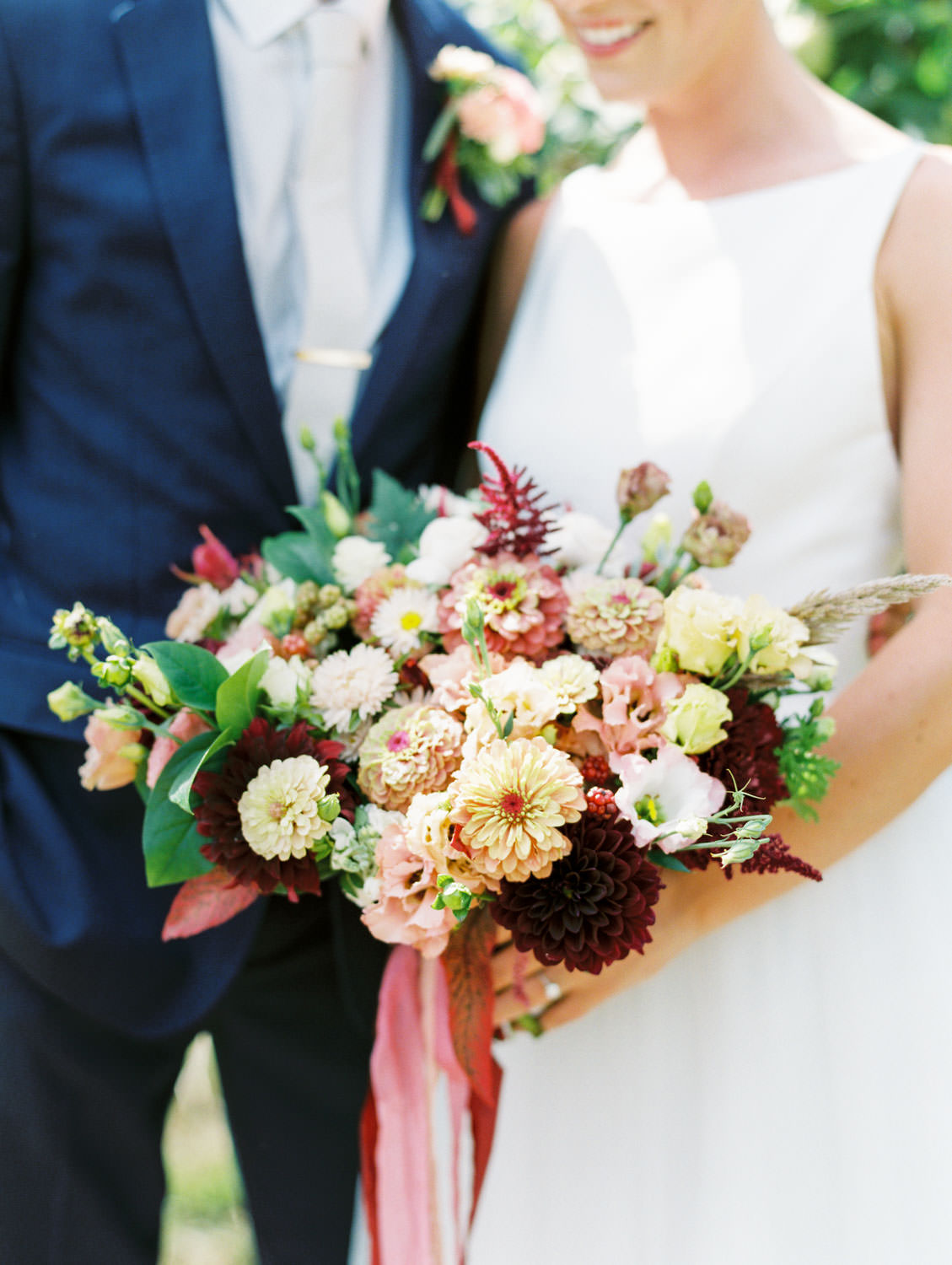 Bride in a classic Mikaella Bridal gown smiling at the camera with the groom in a navy linen suit. Bridal bouquet with ivory, peach, wine, blush flowers and mauve, wine, and blush ribbons. Film photographer Cavin Elizabeth Photography