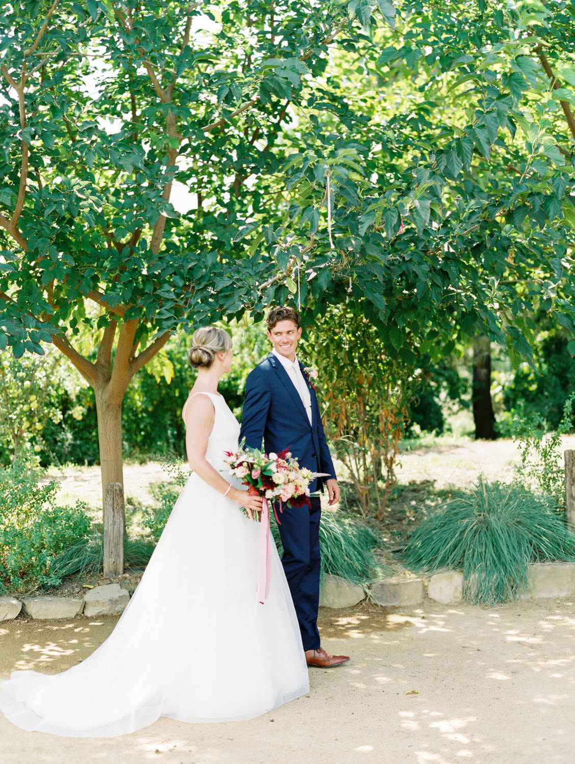 Bride in a classic Mikaella Bridal gown walking with the groom in a navy linen suit. Bridal bouquet with ivory, peach, wine, blush flowers and mauve, wine, and blush ribbons. Full Belly Farm on Martha Stewart Weddings by film photographer Cavin Elizabeth Photography