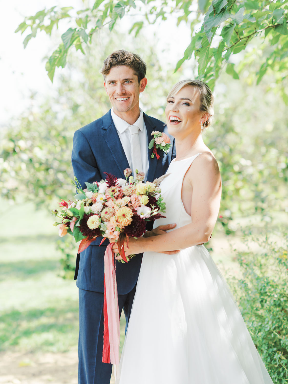 Bride in a classic Mikaella Bridal gown laughing with the groom in a navy linen suit. Bridal bouquet with ivory, peach, wine, blush flowers and mauve, wine, and blush ribbons. Full Belly Farm on Martha Stewart Weddings by film photographer Cavin Elizabeth Photography