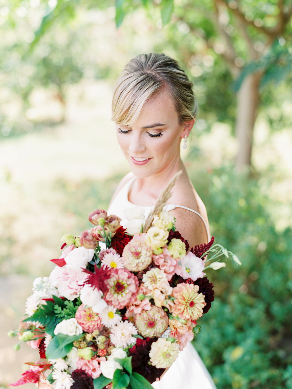Bride in a classic Mikaella Bridal gown smiling at her bridal bouquet with ivory, peach, wine, blush flowers and mauve, wine, and blush ribbons. Martha Stewart Weddings by film photographer Cavin Elizabeth Photography
