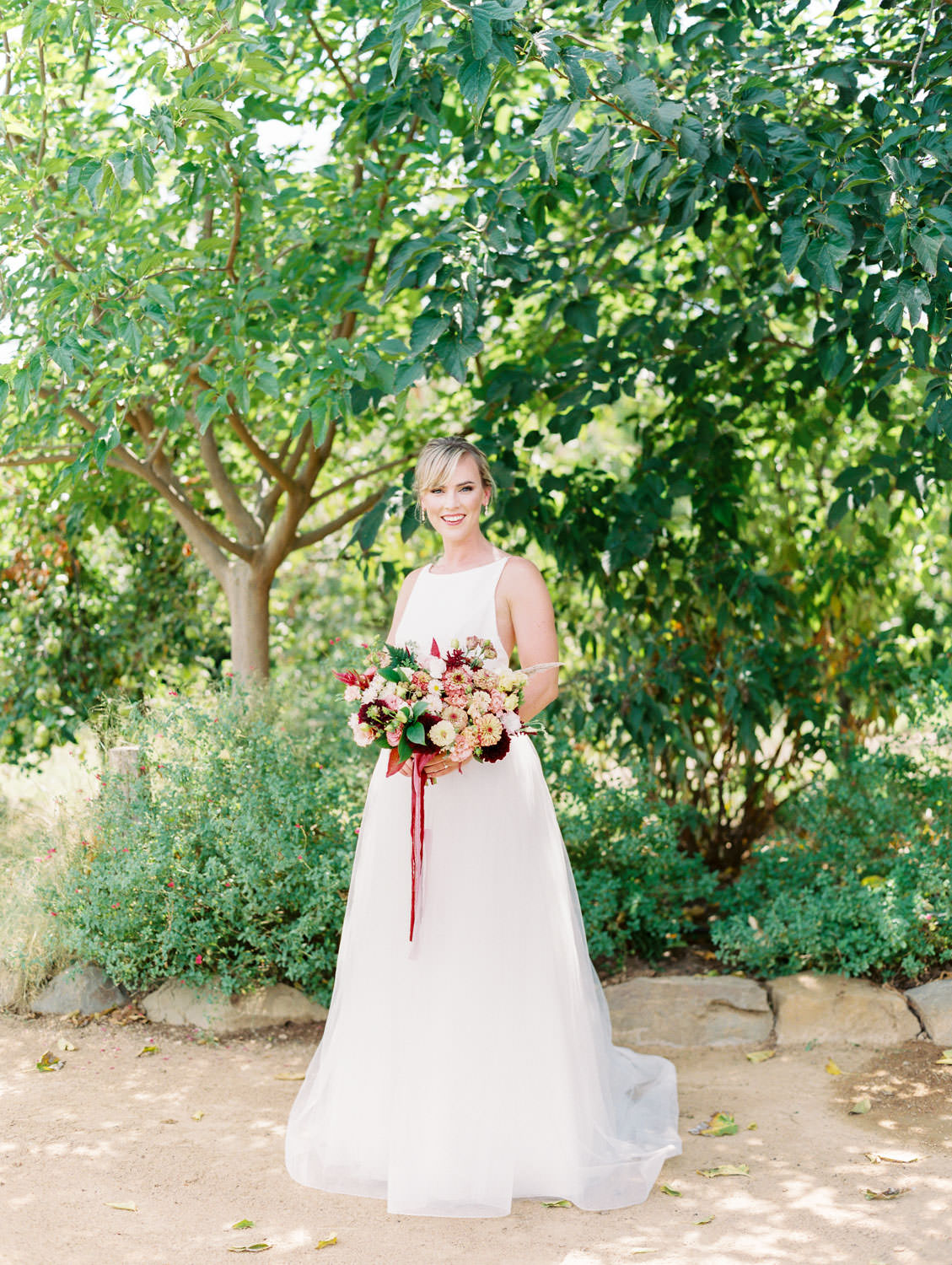 Bride in a classic Mikaella Bridal gown holding her bridal bouquet with ivory, peach, wine, blush flowers and mauve, wine, and blush ribbons. Martha Stewart Weddings by film photographer Cavin Elizabeth Photography