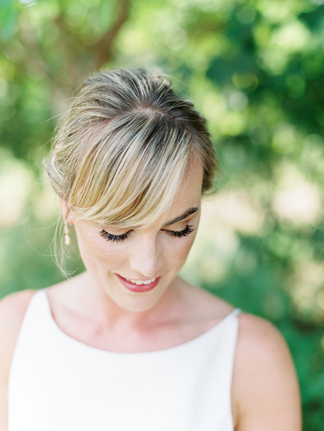 Bride in scoop neck gown with updo and bangs down. Natural bridal makeup. Martha Stewart Weddings by film photographer Cavin Elizabeth Photography