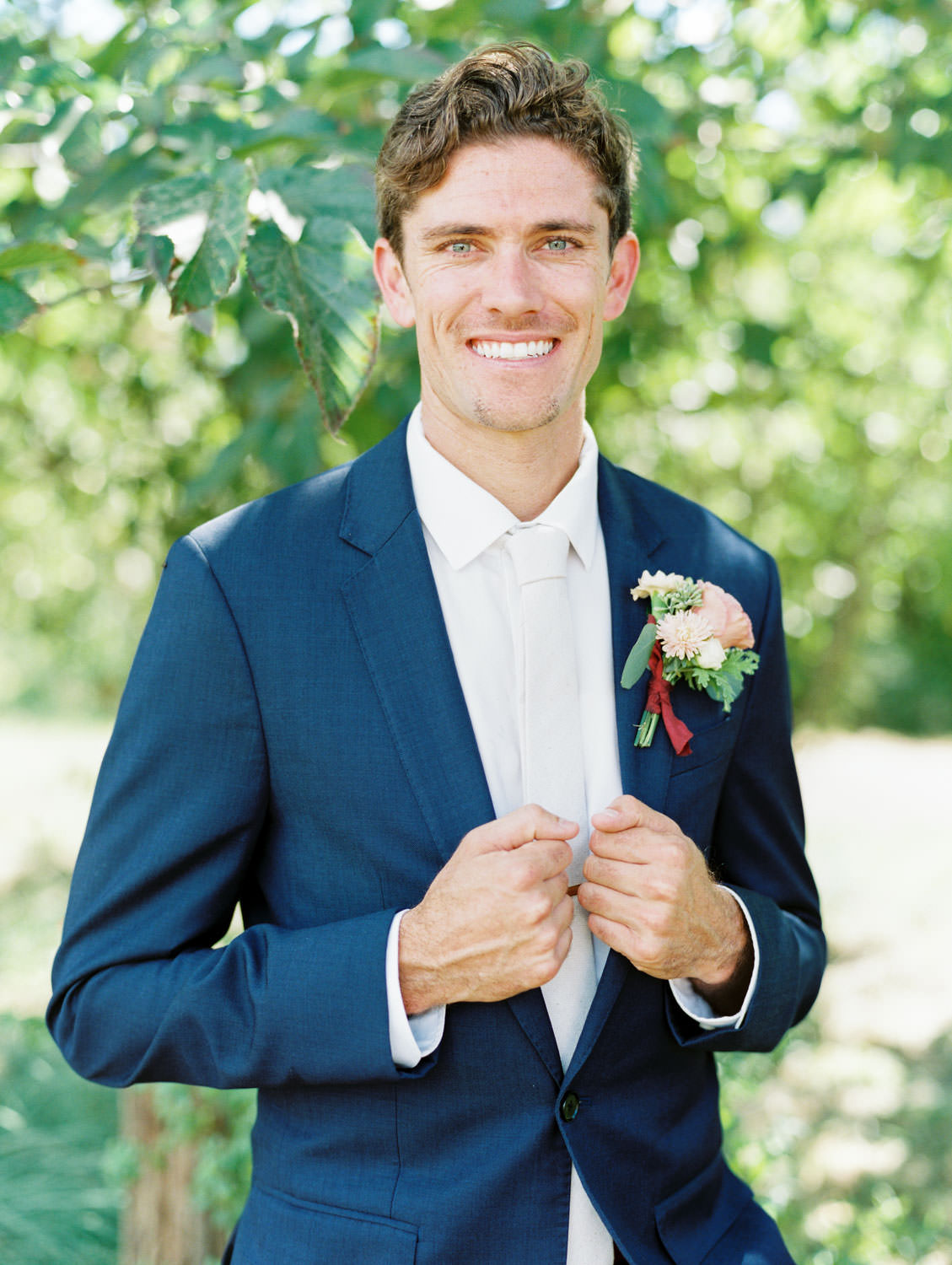 Groom in navy linen suit with ivory tie and large boutonniere with peach and green flowers. Cavin Elizabeth Photography.