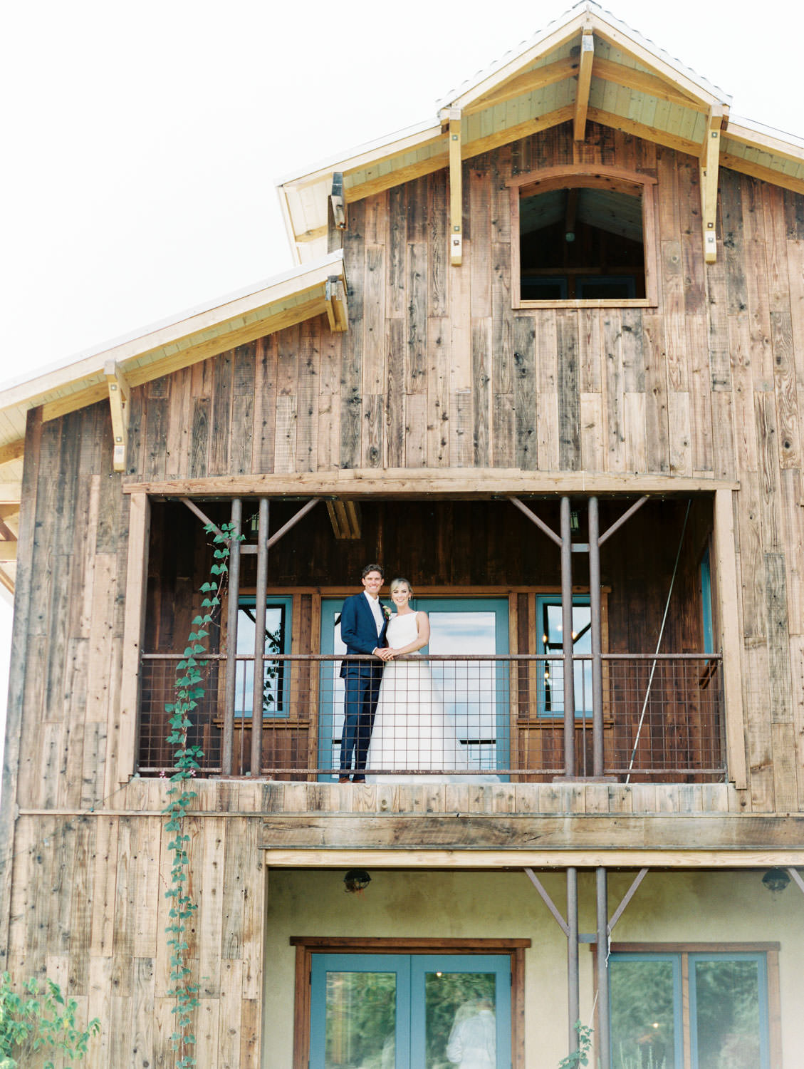 Bride in a classic Mikaella Bridal gown laughing with the groom in a navy linen suit on the balcony of the farm house. Full Belly Farm on Martha Stewart Weddings by film photographer Cavin Elizabeth Photography