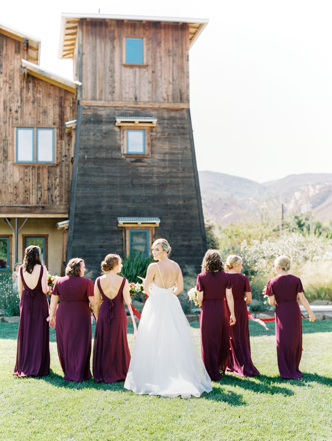 Bridesmaids in deep wine gowns by Show Me Your Mumu walking with the bride. Full Belly Farm on Martha Stewart Weddings by film photographer Cavin Elizabeth Photography