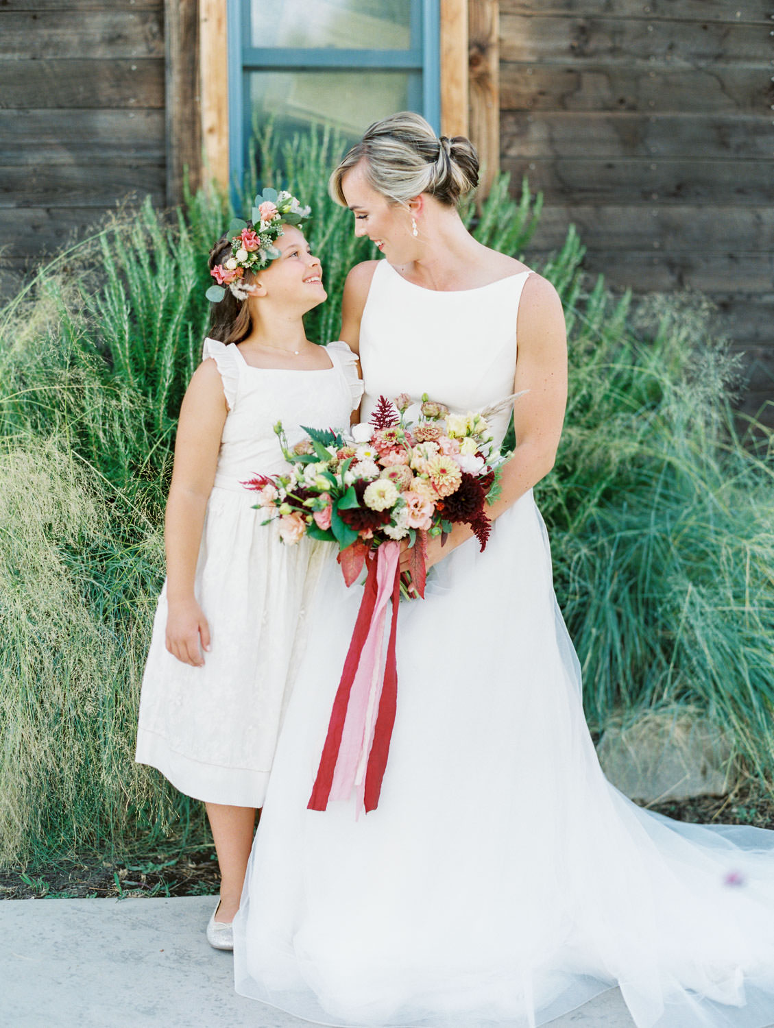 Flower girl in floral crown smiling at the bride in a classic Mikaella Bridal gown holding her bridal bouquet with ivory, peach, wine, blush flowers and mauve, wine, and blush ribbons. Martha Stewart Weddings by film photographer Cavin Elizabeth Photography